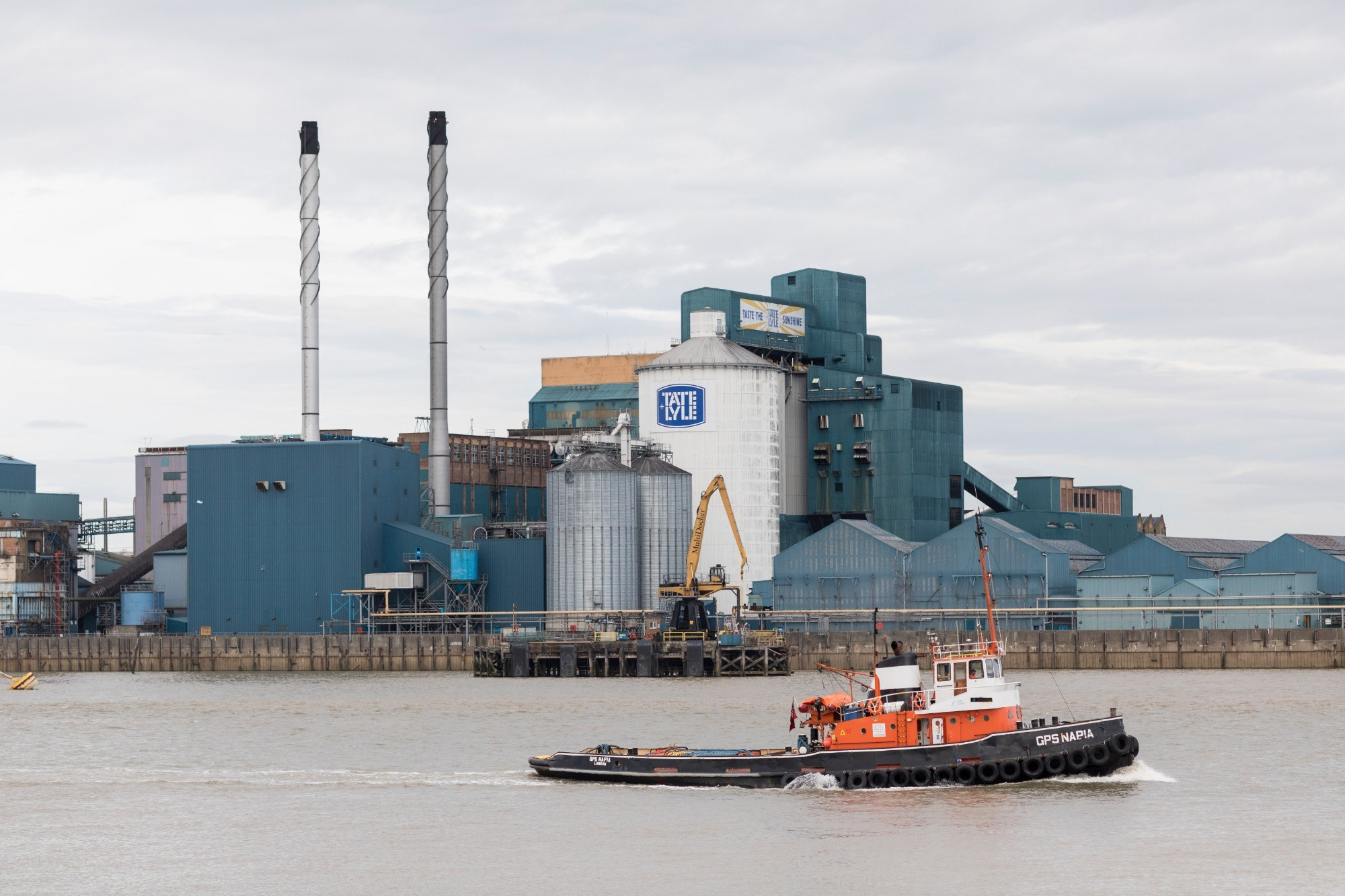 Tate & Lyle building exterior from the river with a boat in the foreground and big chimneys visible