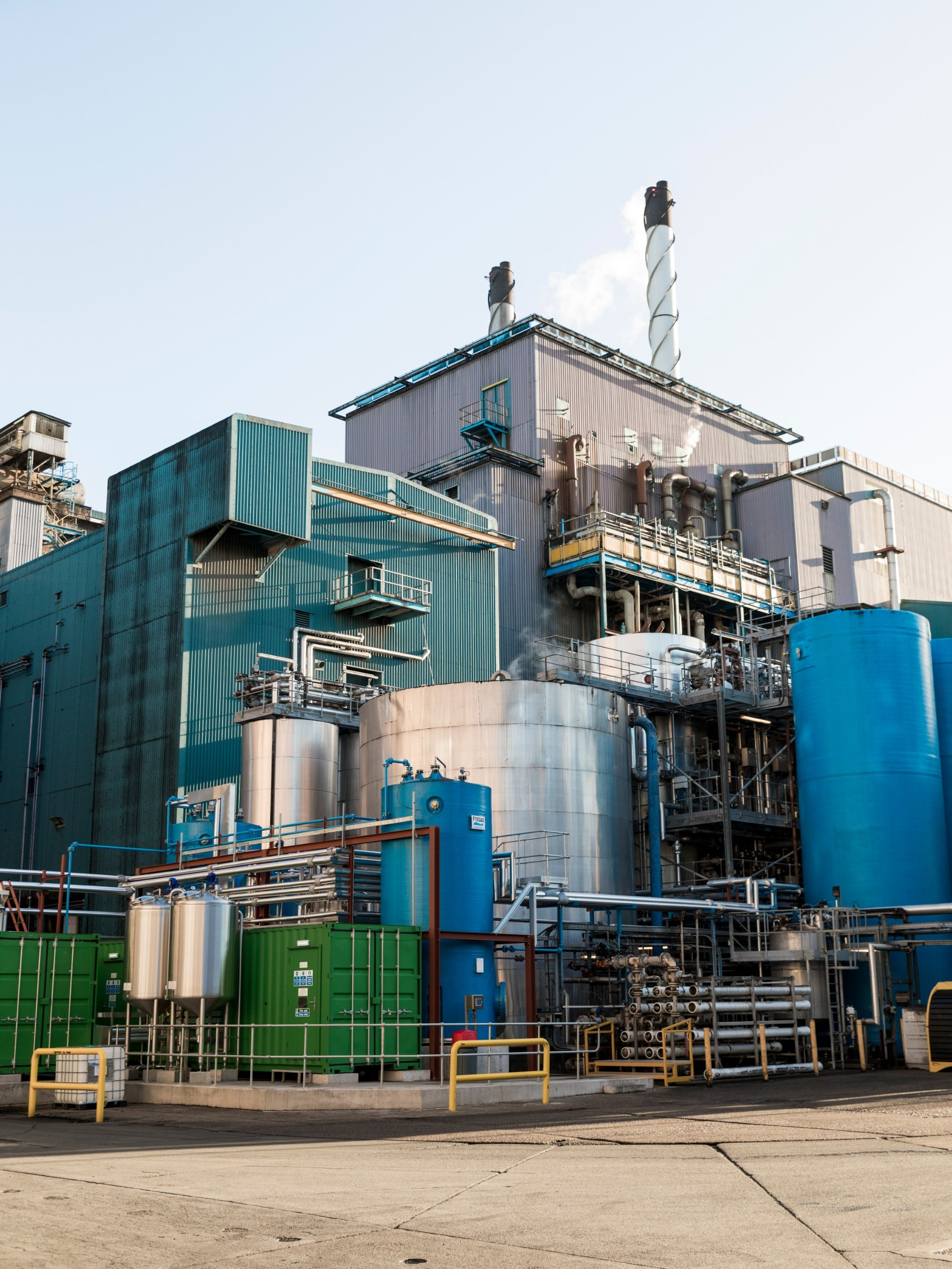 Exterior of a building that looks like a factory, with chimneys and cylindrical structures