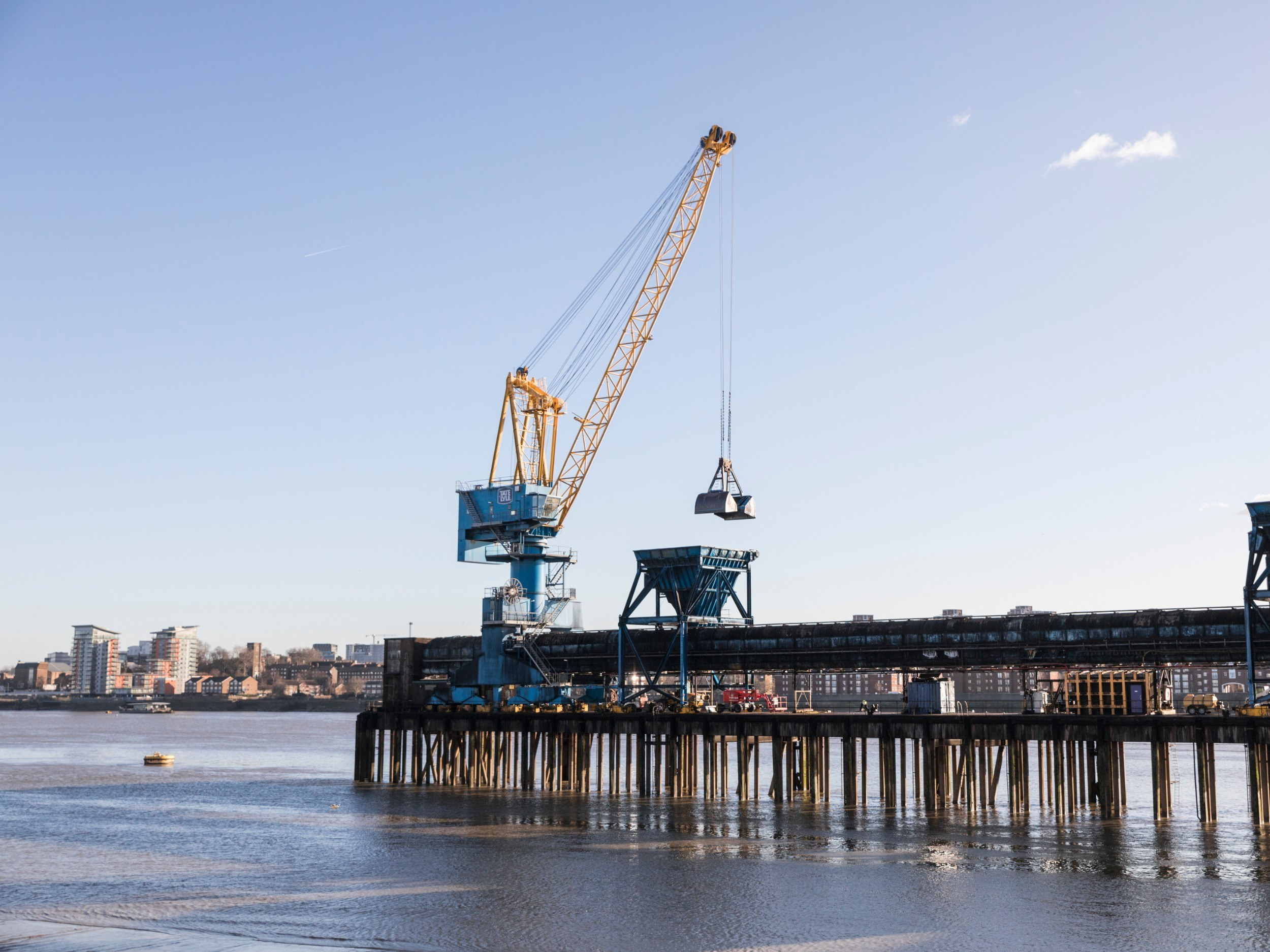 A pier jutting out into the river, with a crane on the end of it