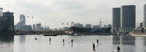 Seven people in wetsuits paddleboarding on the water at the Royal Docks