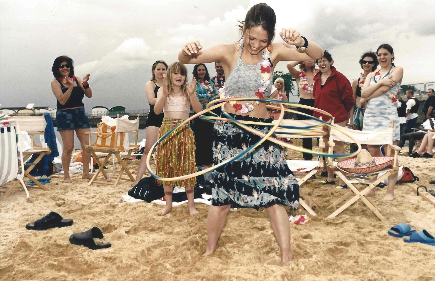 An old photo of young people hula-hooping on the Royal Docks beach