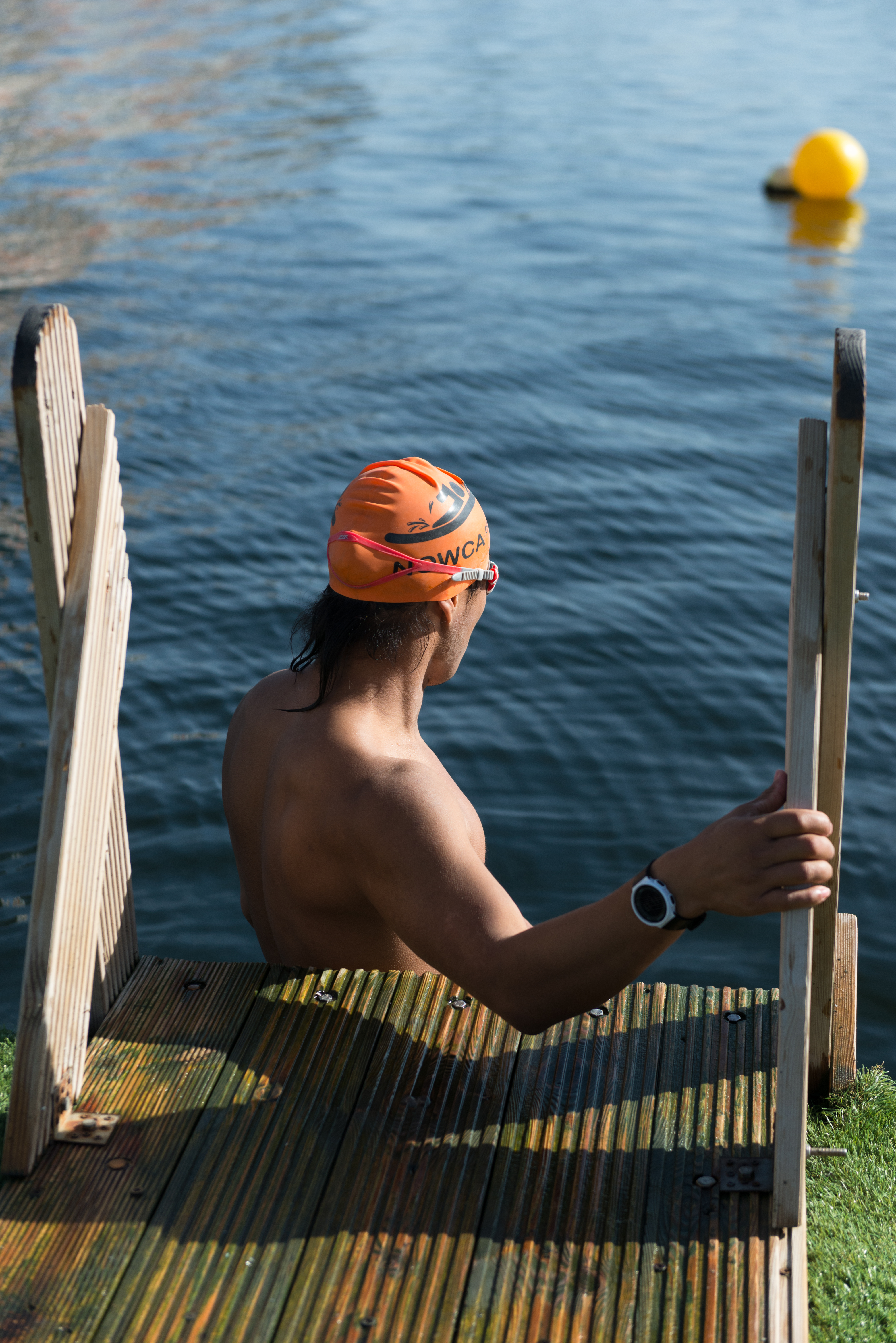 A swimmer in an orange cap about to set out from the dock edge