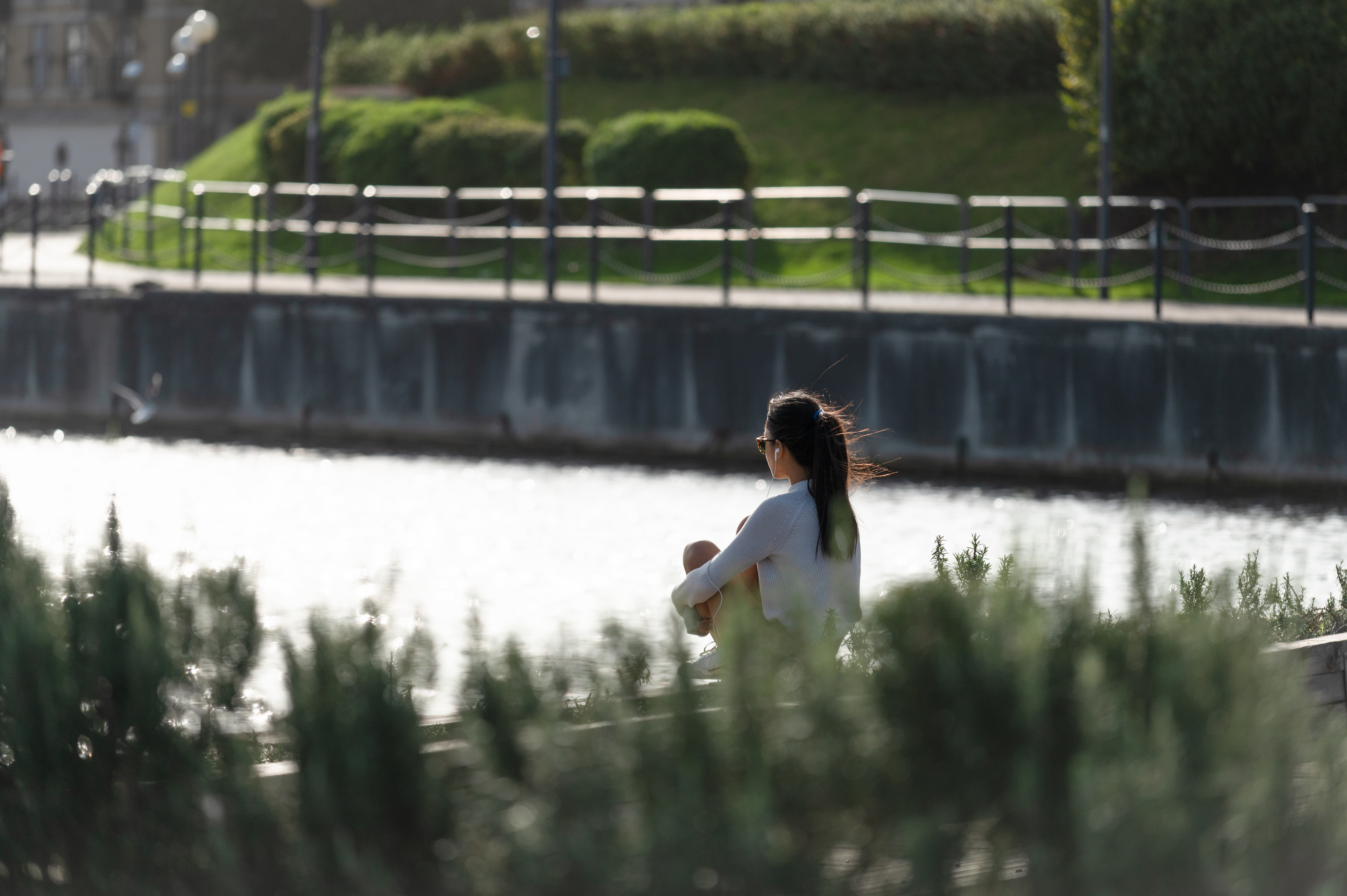 A woman sitting and looking out on the dock water