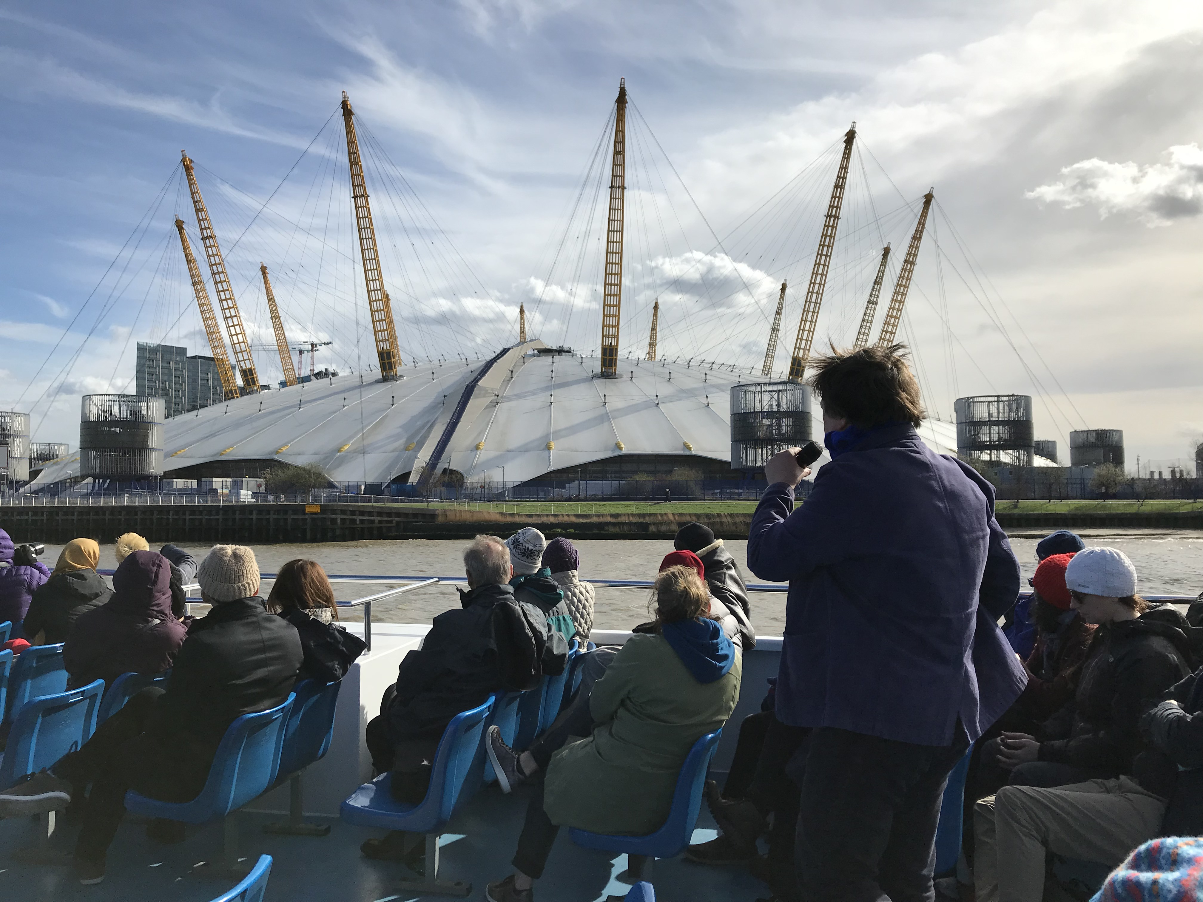 A crowd of people on the Thames East tour taking photos of The O2