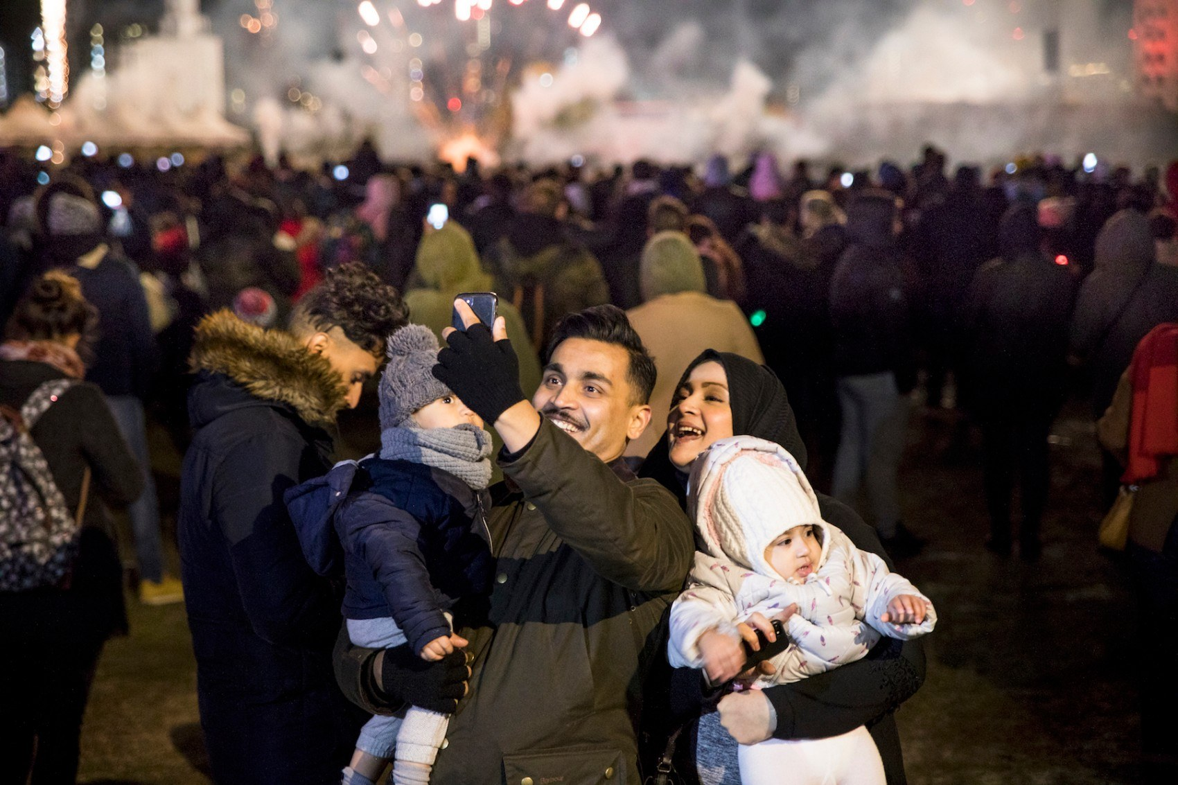 Man and woman holding a child each taking a selfie with fireworks in the background