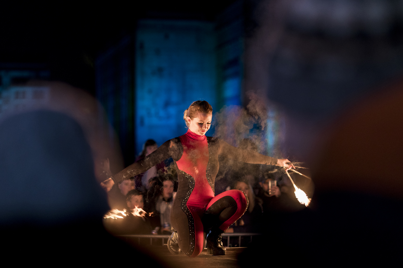 Dancer crouching down twirling sticks with fire on either end