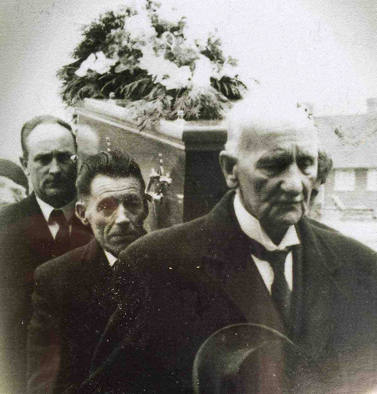 A photograph of three men carrying a coffin