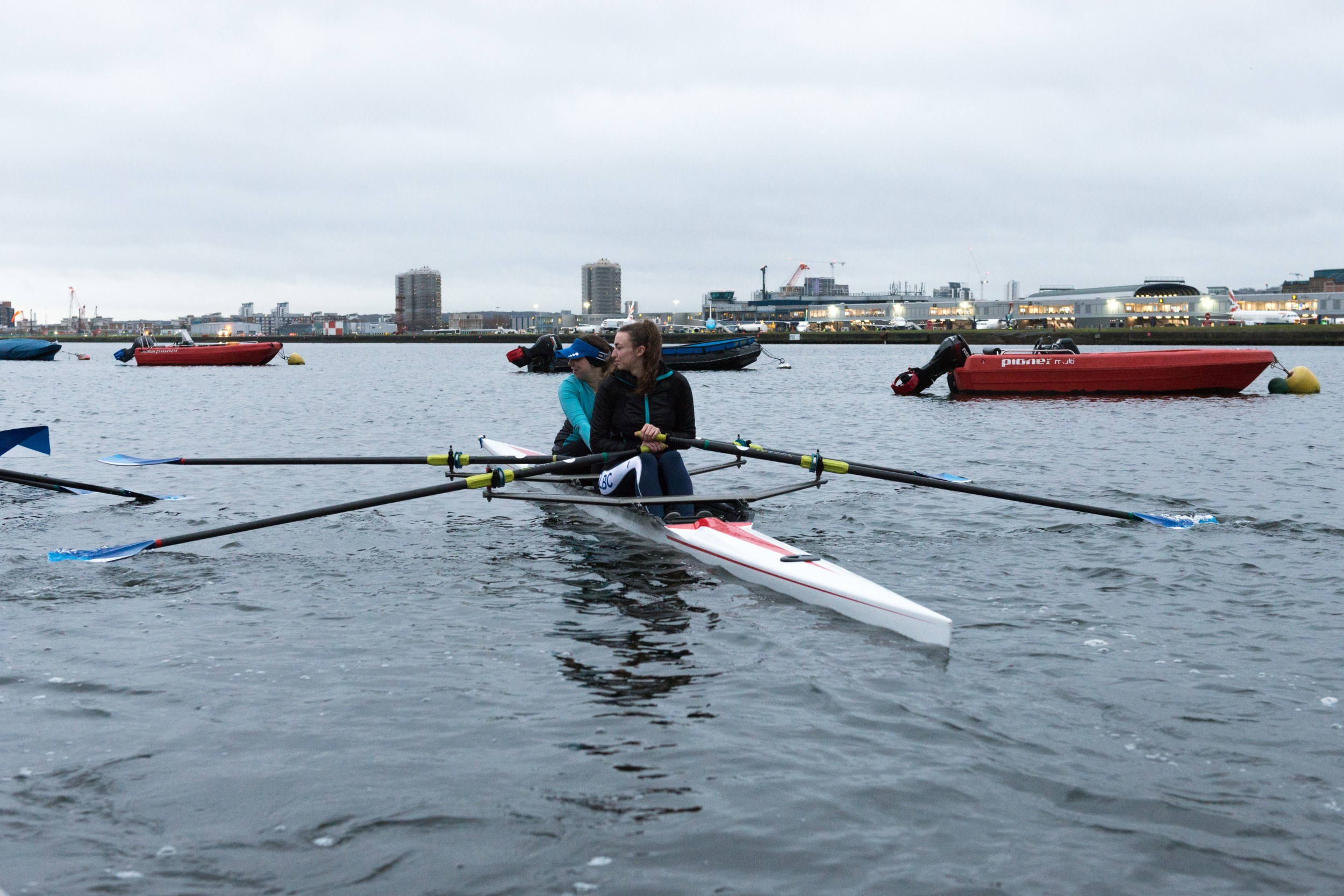 Two women rowing with other boats in the background
