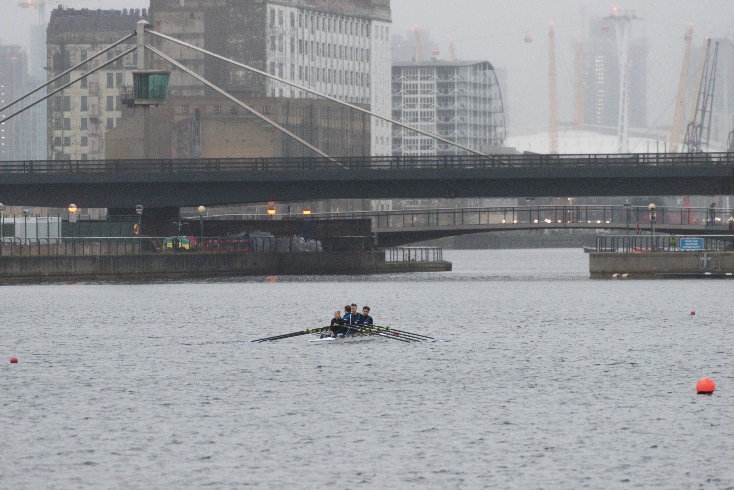 Scene of the docks with a rowing boat and the O2 visible in the background