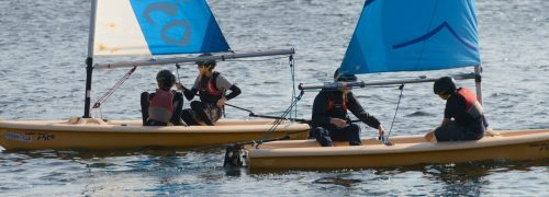 Two small sailing boats being sailed by two young people in each