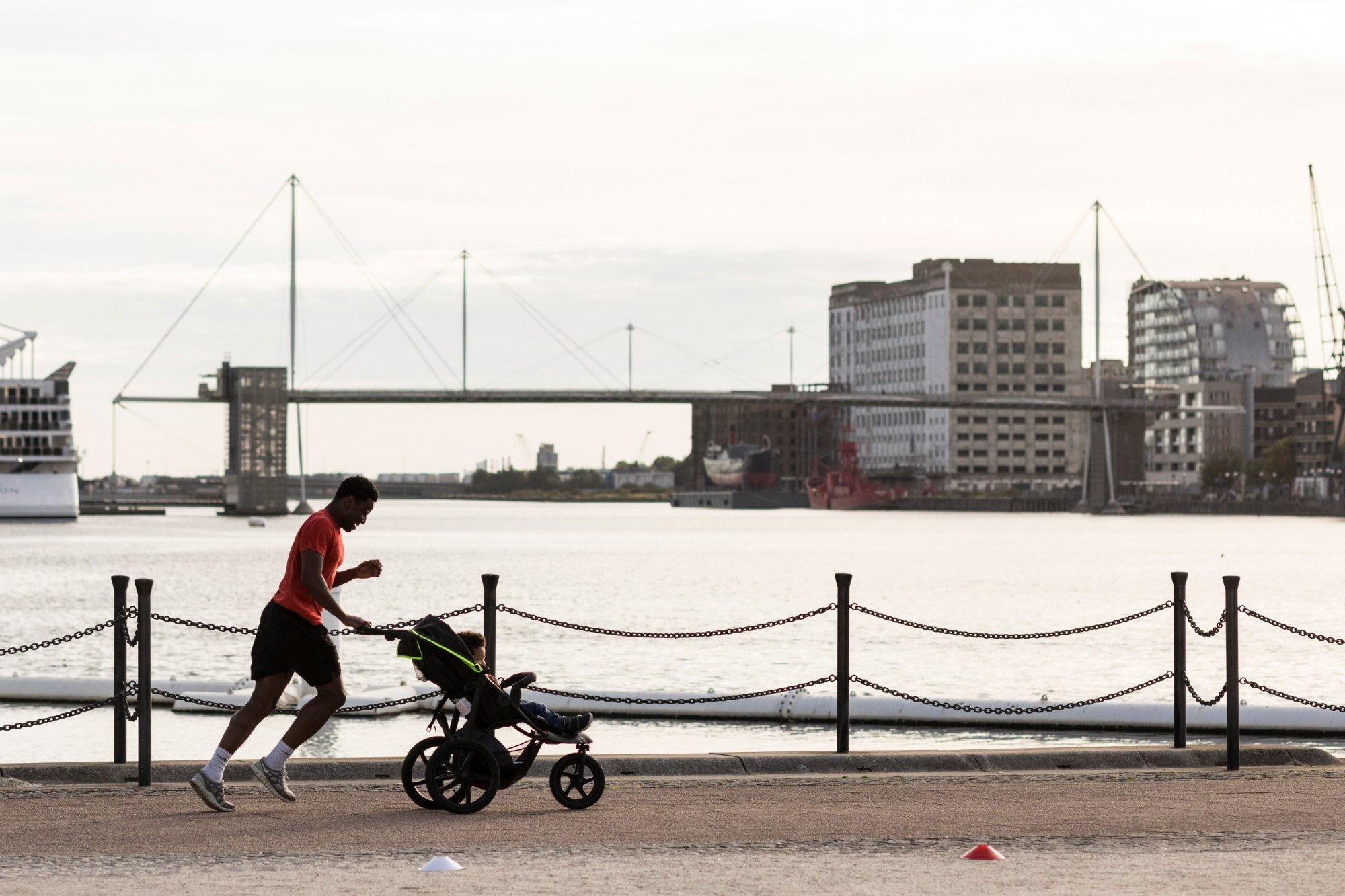 Man running along the edge of the dock with a buggy and a child