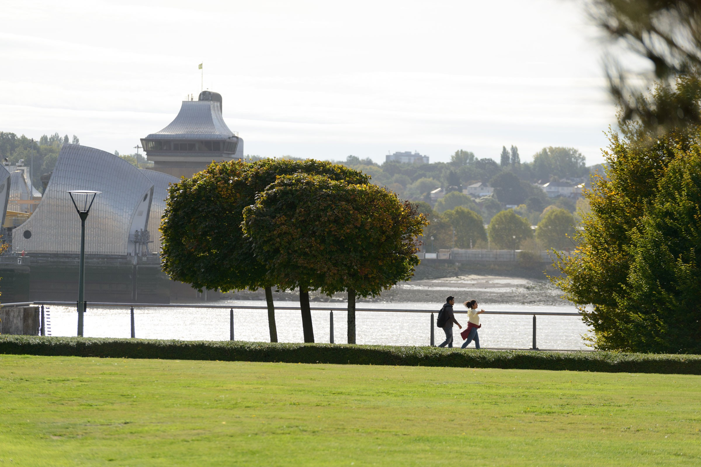 People walking in Thames Barrier Park with the river as backdrop