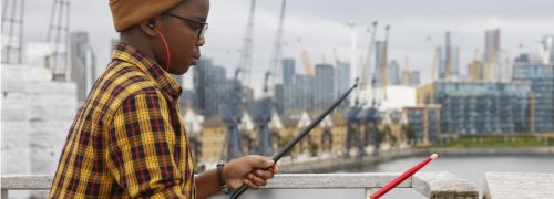 Child using drum sticks on railing at the Royal Docks