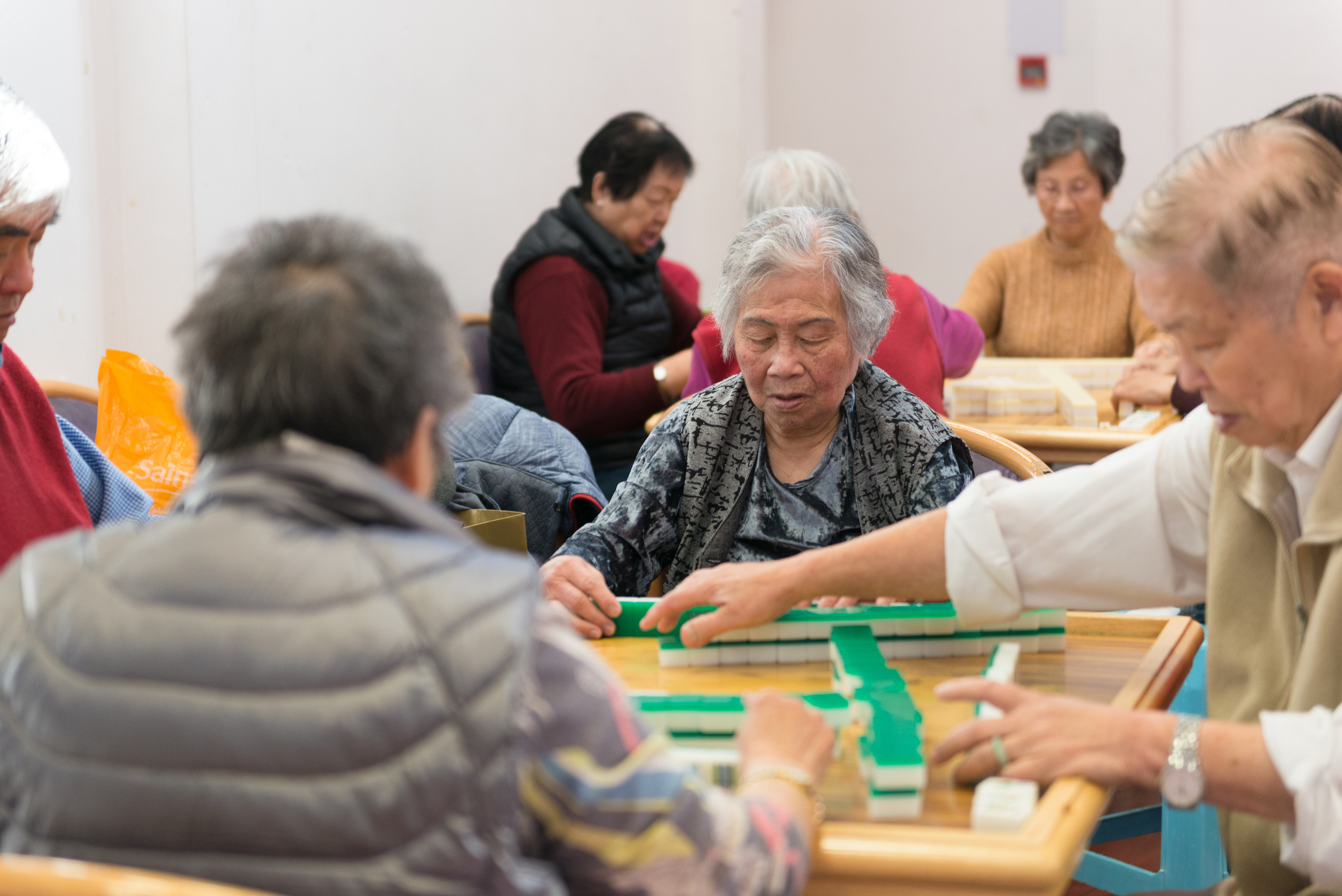 Scene of 8 people playing a table top tile game in groups of four