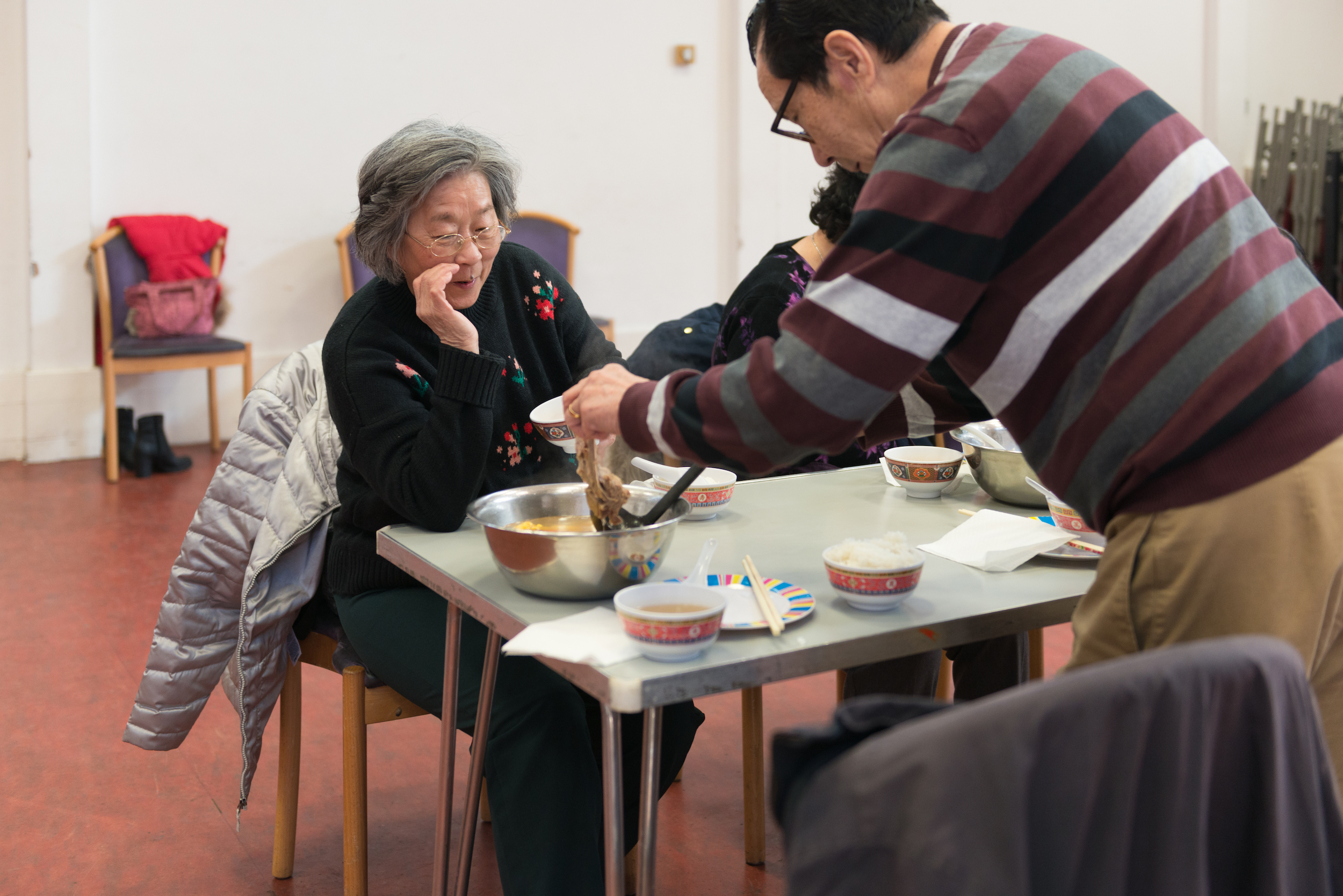 Man serving lunch, with two women sitting around a table