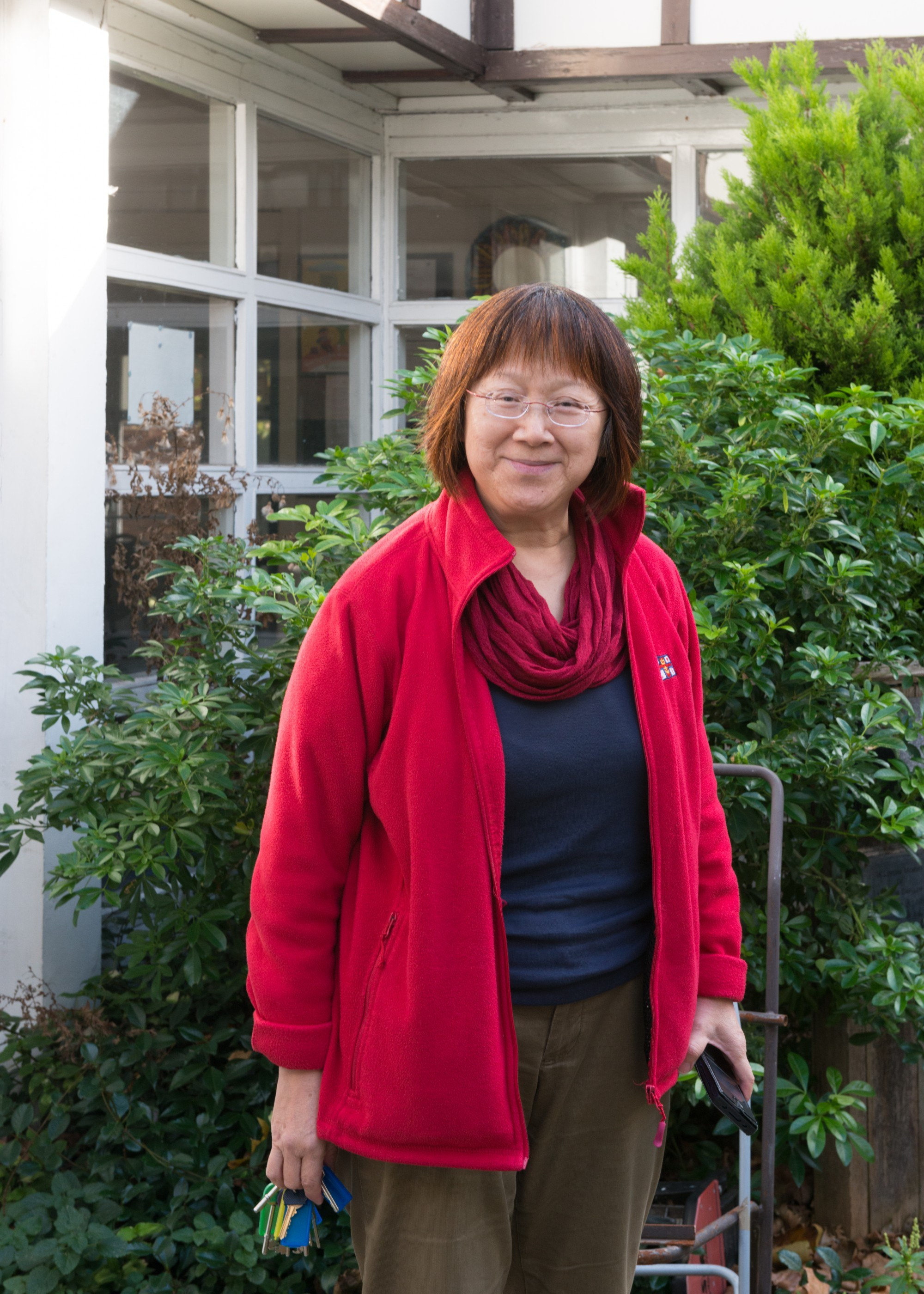 Portrait of Gill Tan, smiling slightly, outside with foliage in the background