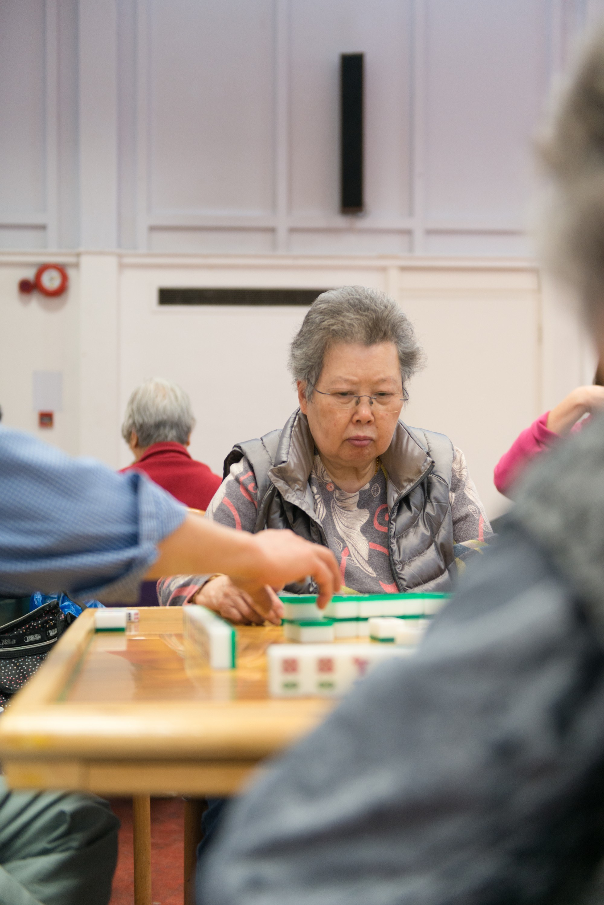 Woman playing tile-based game with look of concentration