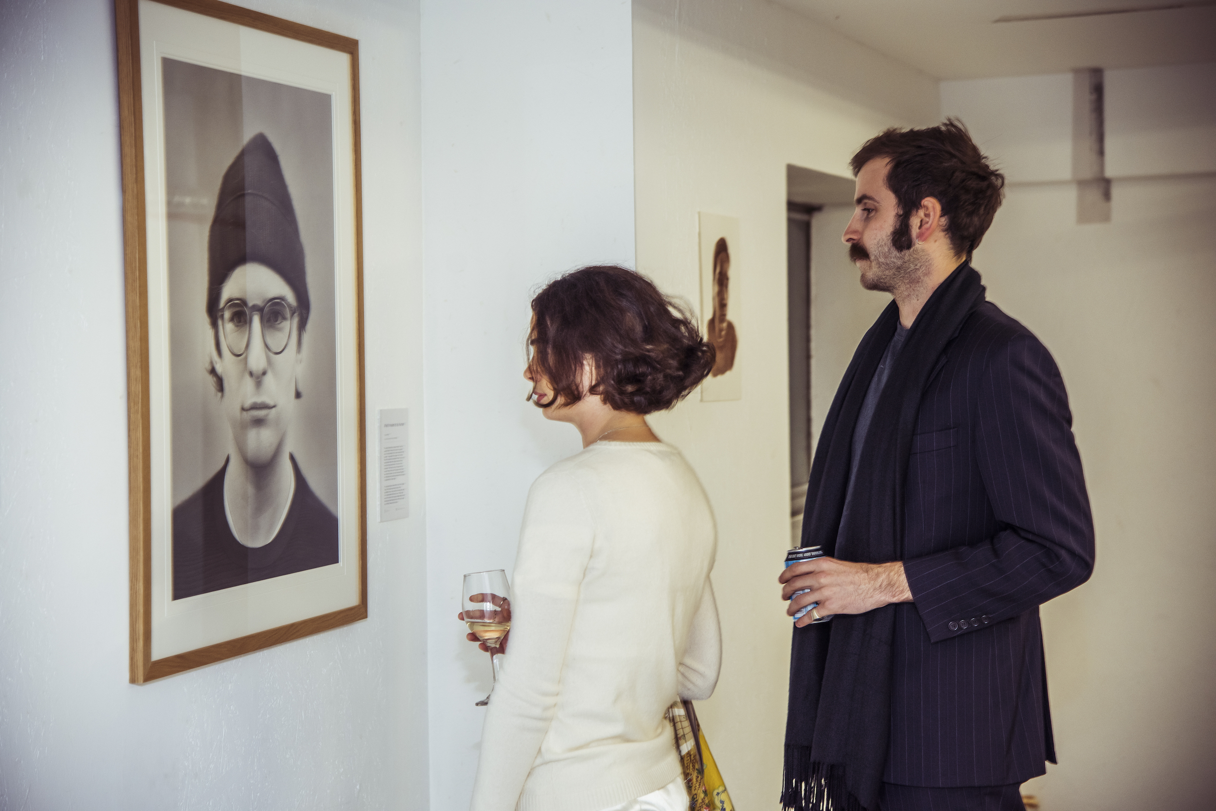 Two people looking at a photograph hanging on the wall