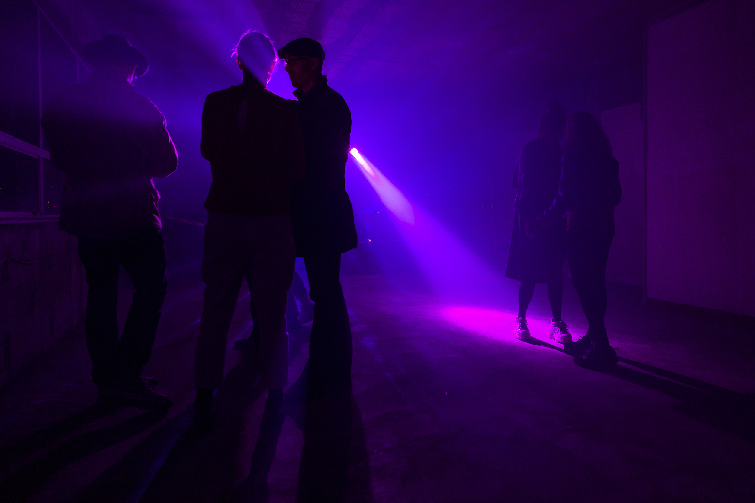 Dark room with purple lighting and silhouettes of a few people in the foreground