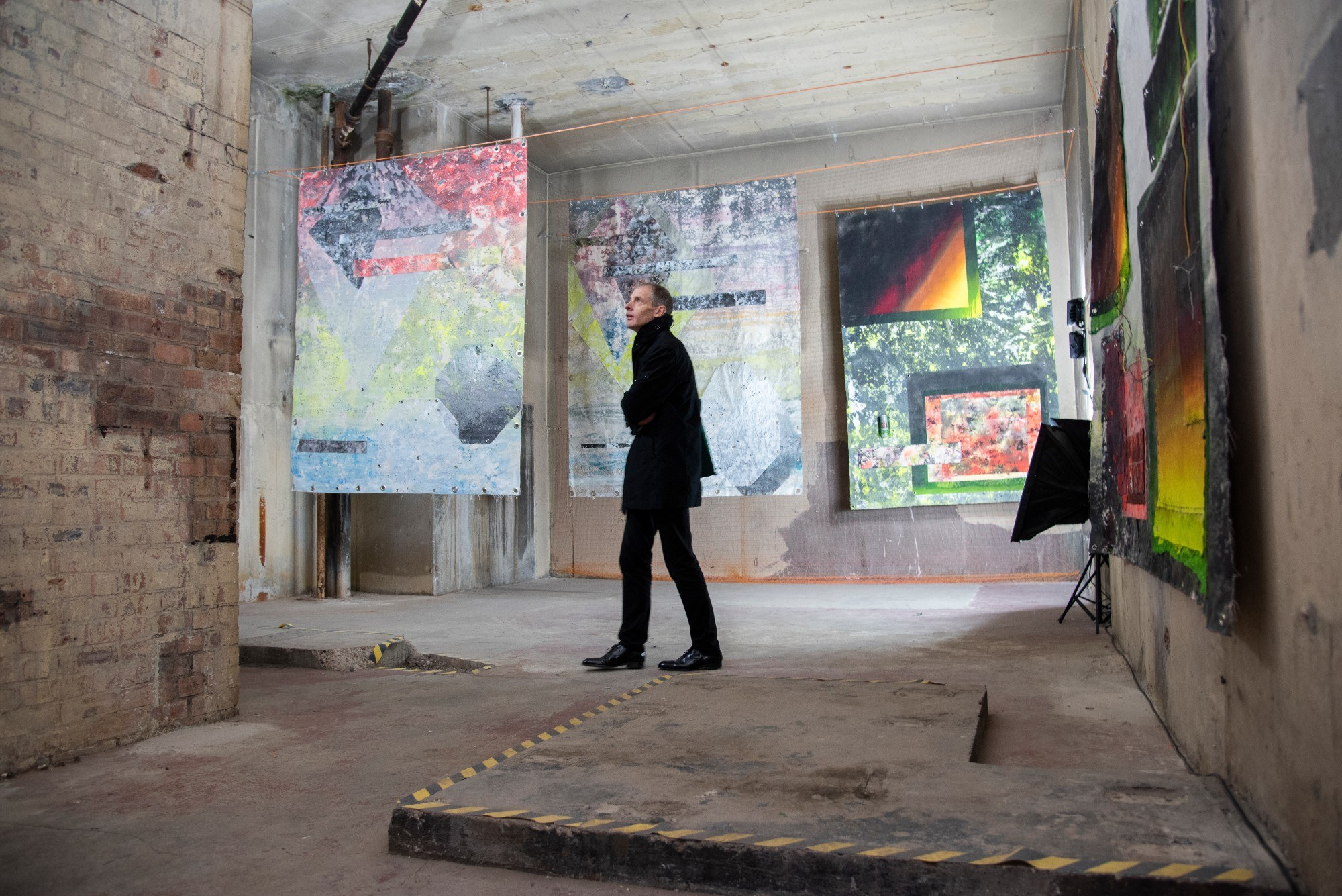 Man looking at large abstract paintings in room with concrete walls