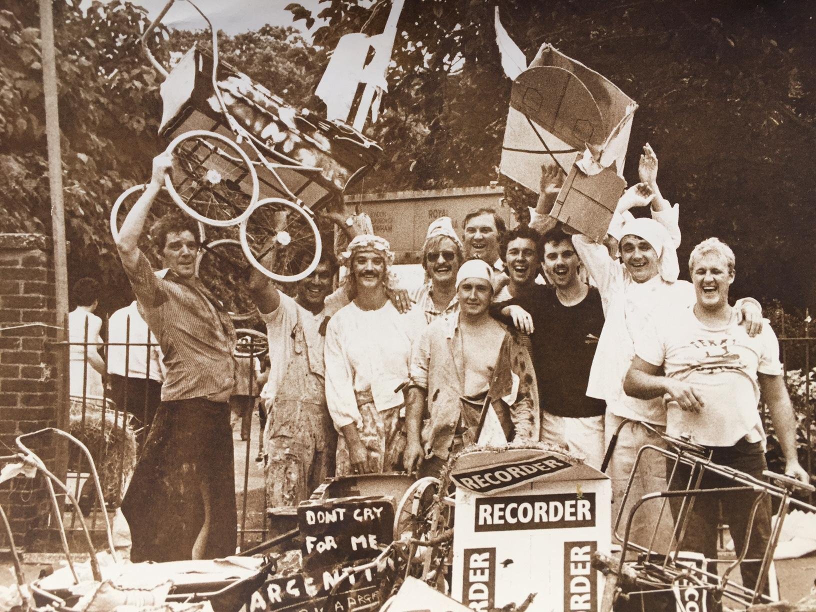Group of men smiling, wearing costumes. One is waving a pram in the air.