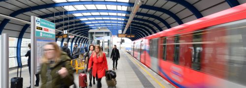 A DLR station platform with a departing DLR train.