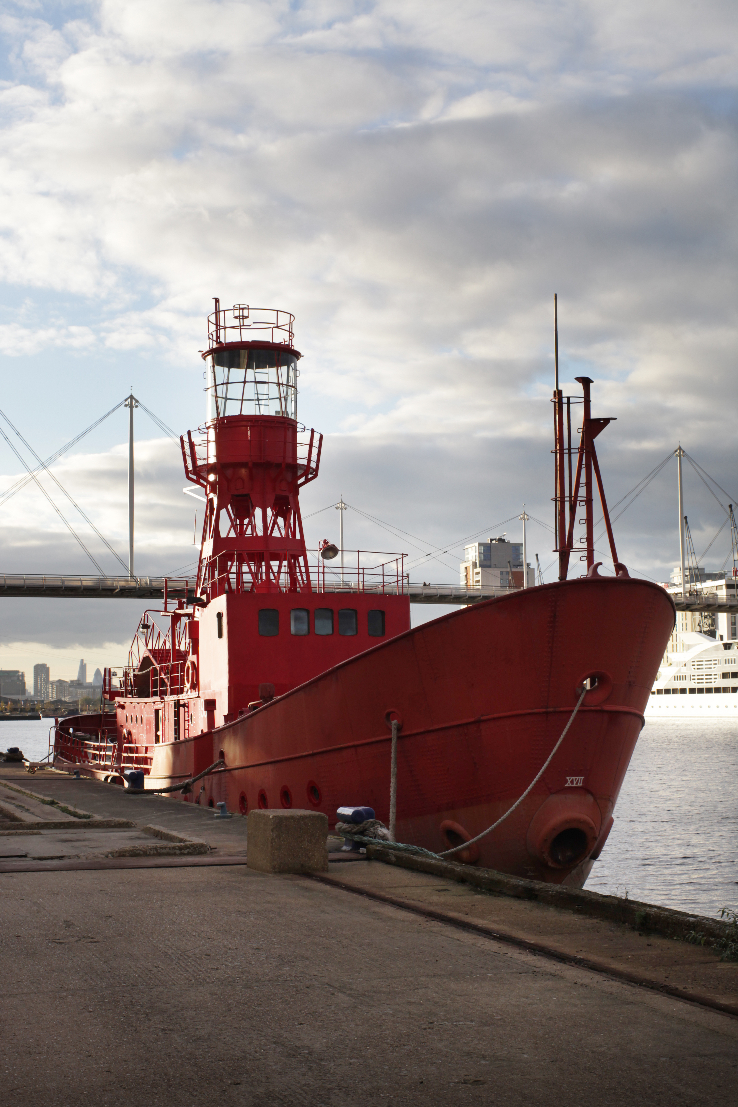Red boat with lighthouse tower moored on the edge of the dock