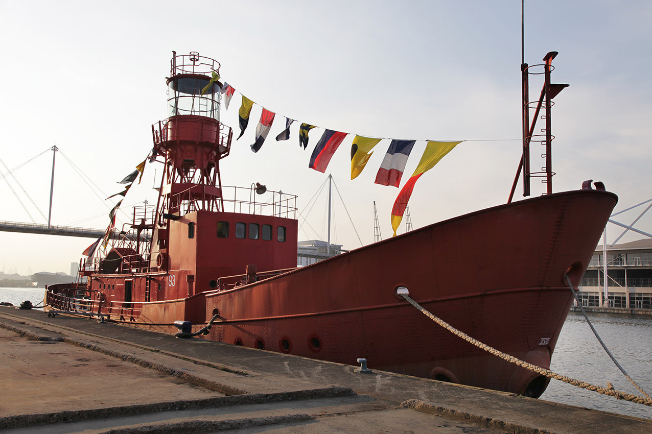 Red boat with lighthouse tower and flags moored on the edge of the dock