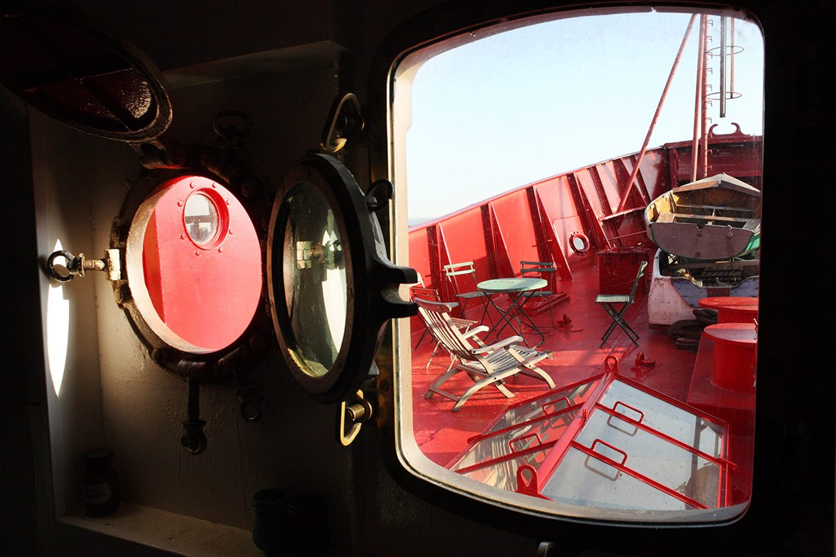 Looking out from an opening in the boat onto the red deck at one end