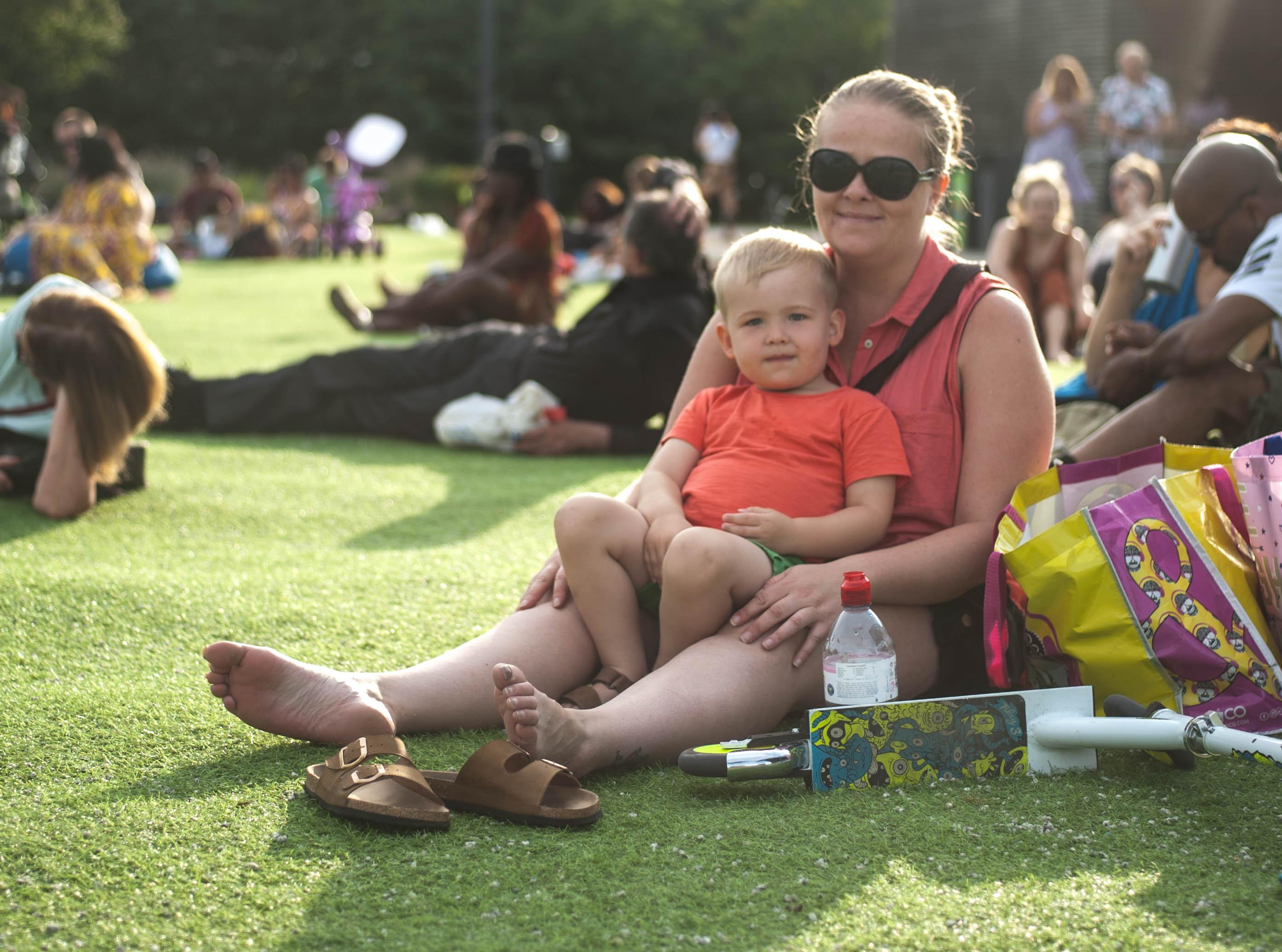 A woman sat with child on the grass