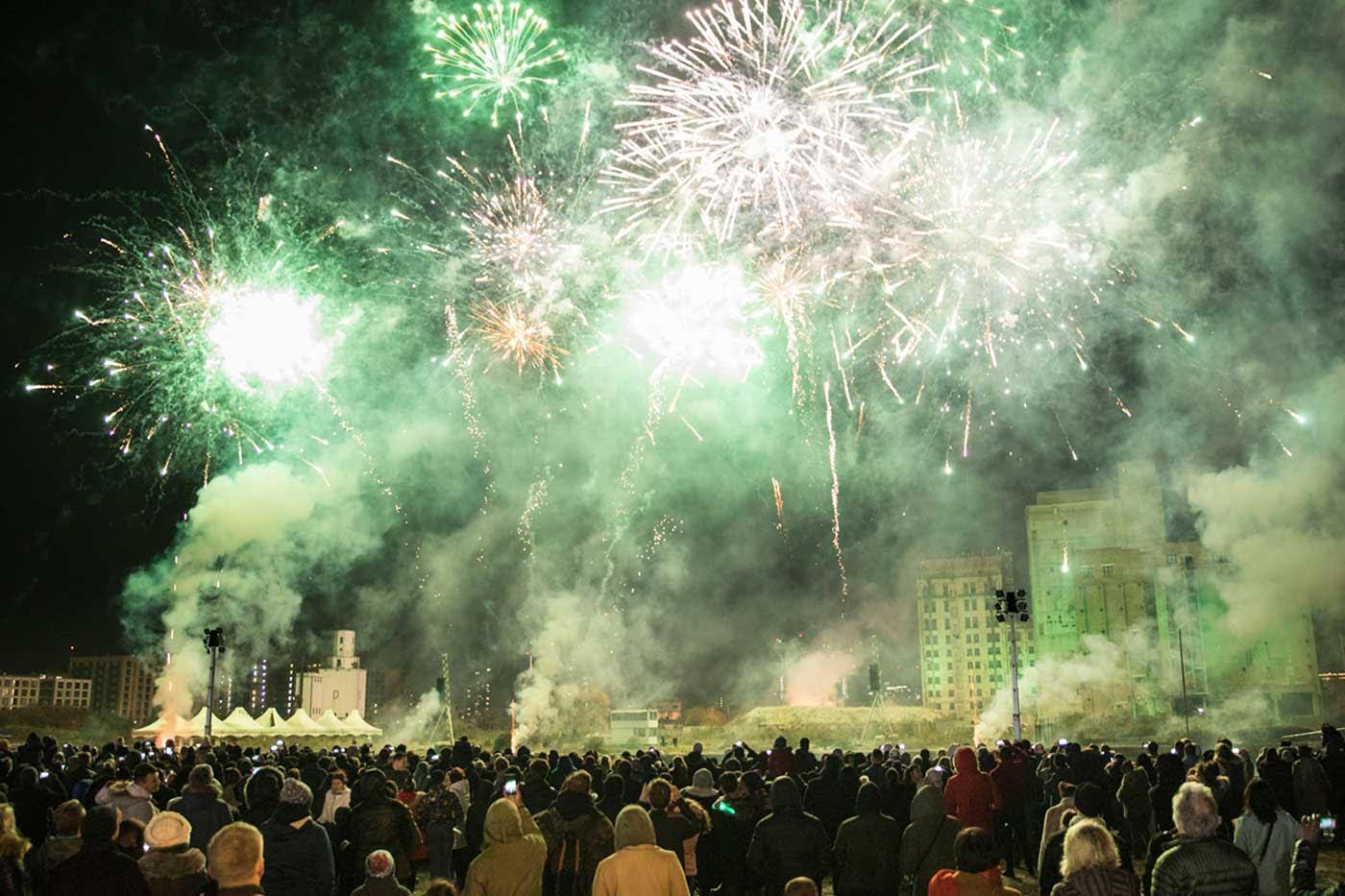 Bright green and white fireworks exploding over a large onlooking crowd