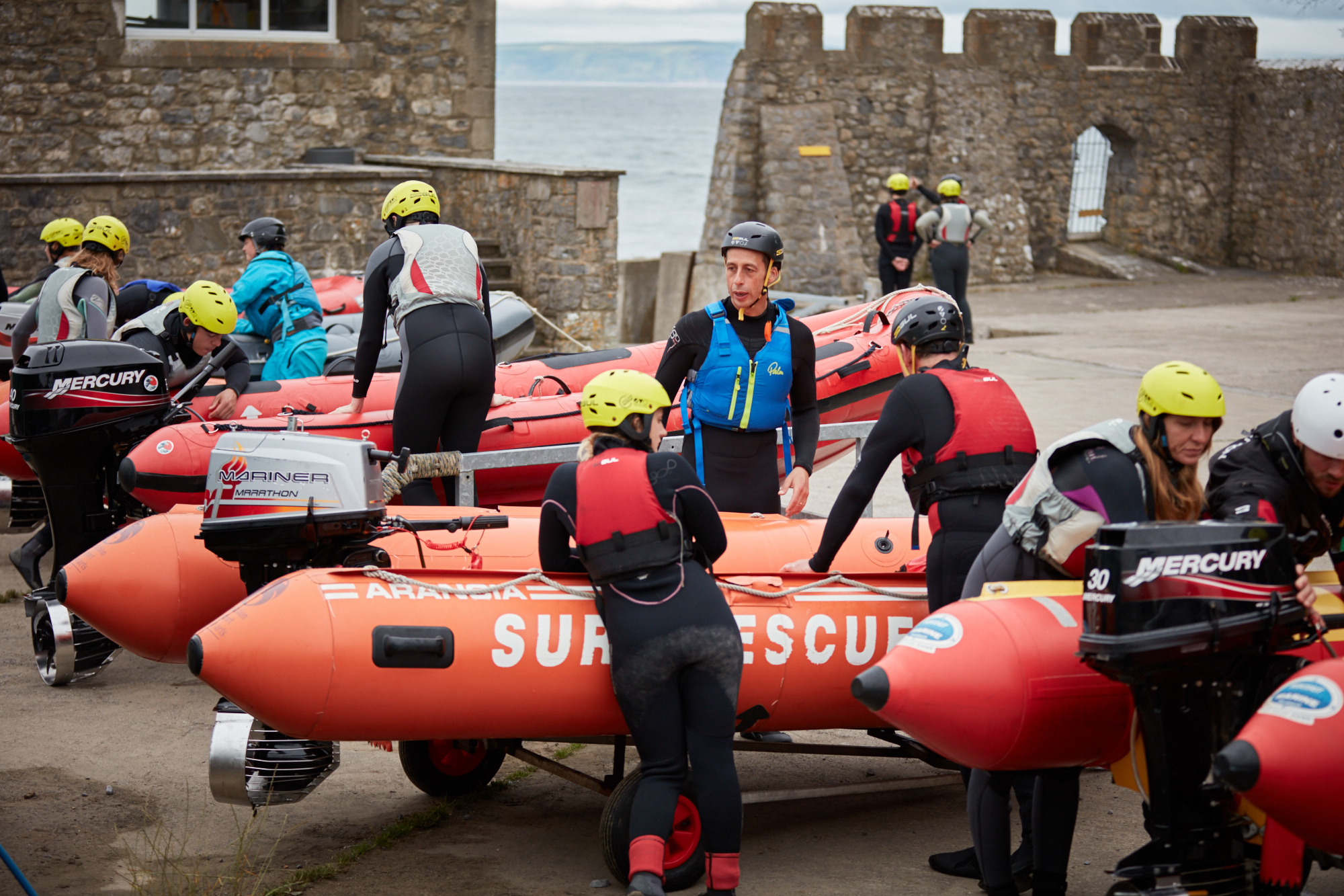 A group of people in wetsuits surrounding a group of four lifeboats