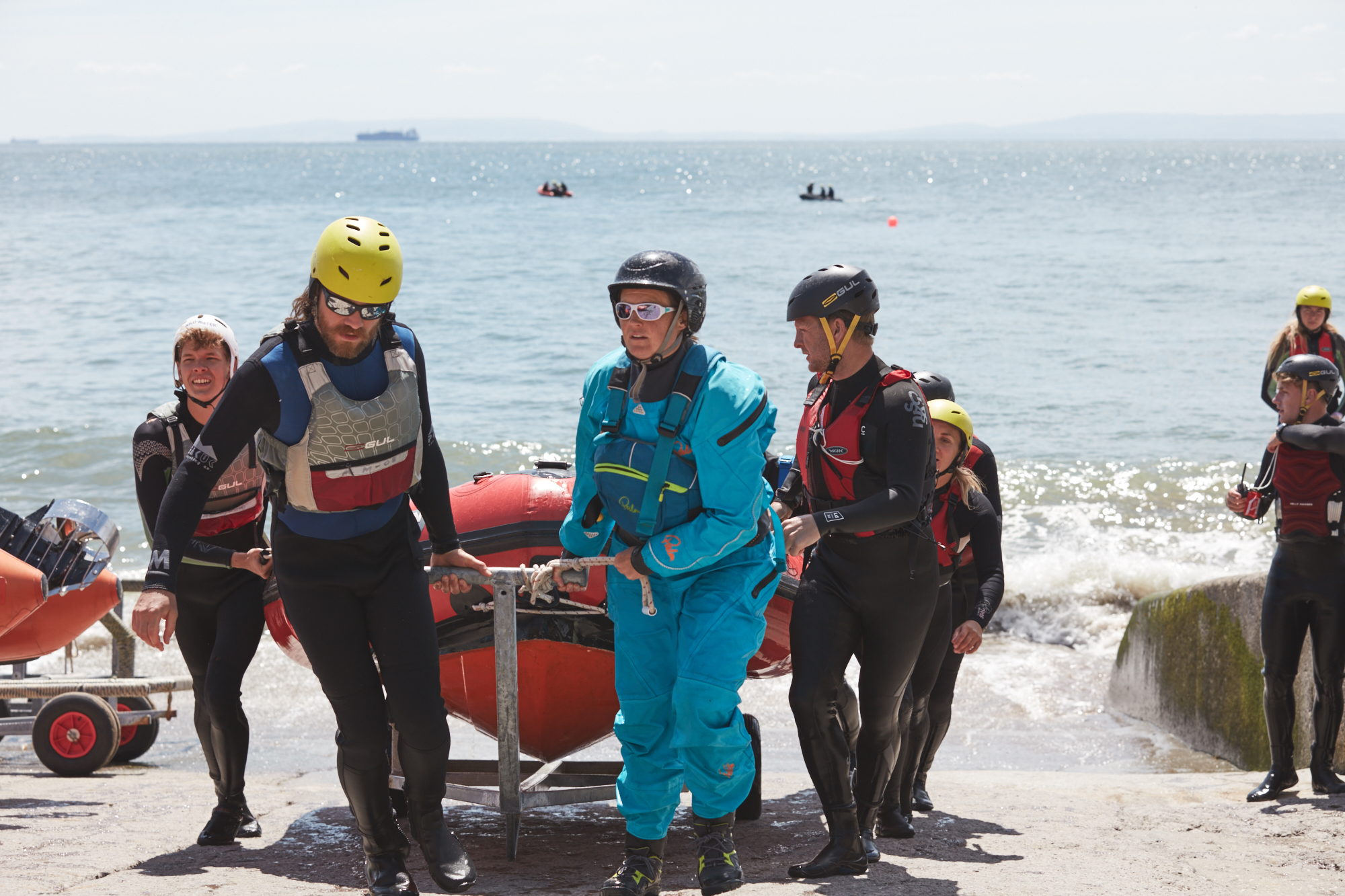 A group of people in wetsuits and lifejackets bringing a lifeboat out of the water