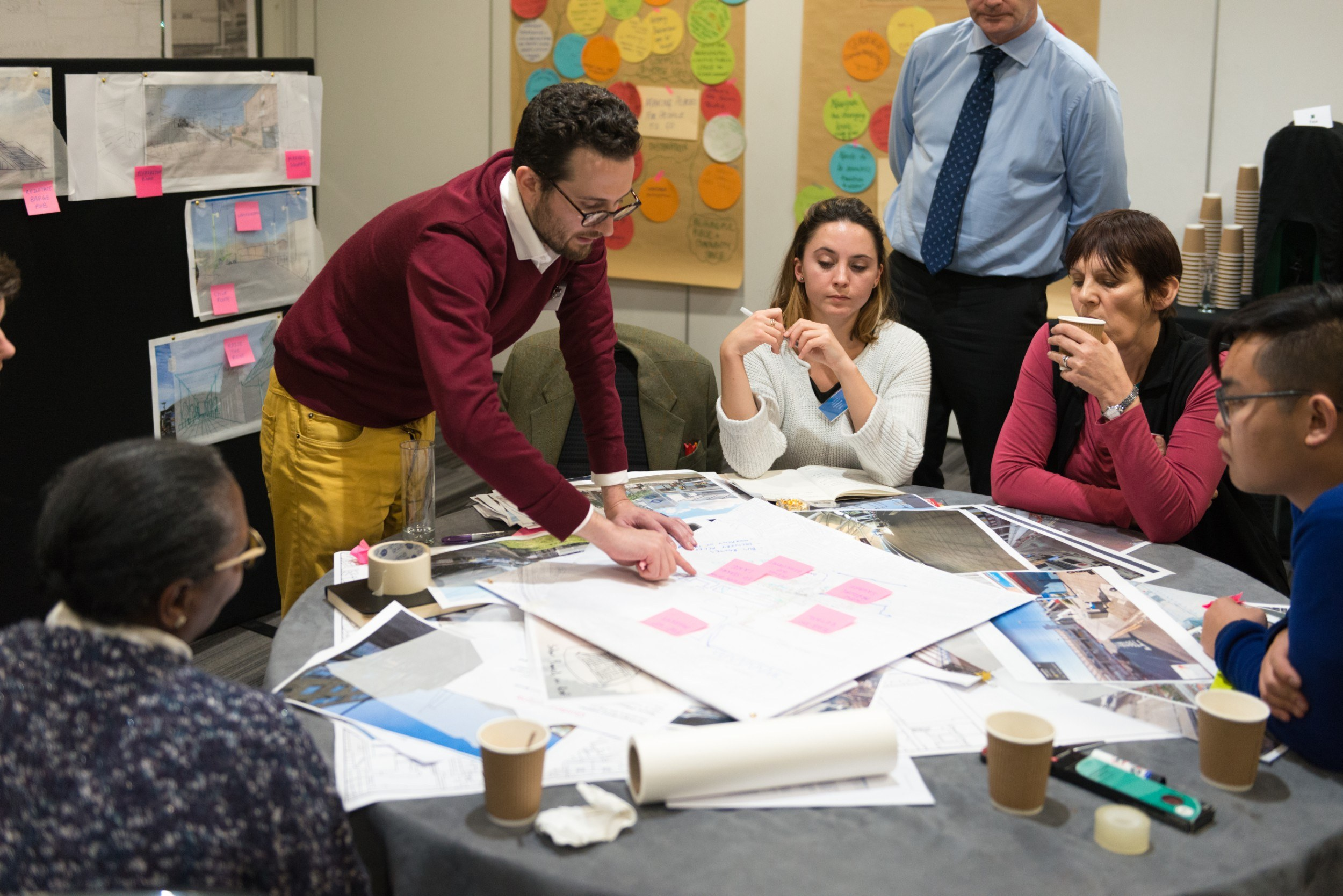 Group of people around a table poring over large pieces of paper
