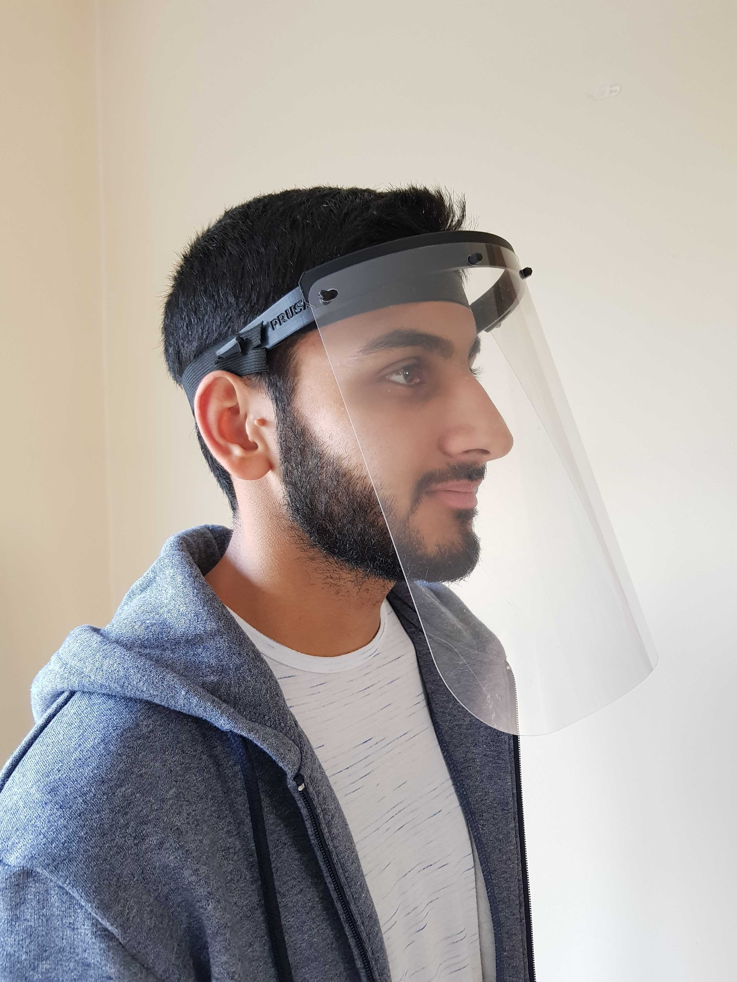 Young man wearing a plastic face visor