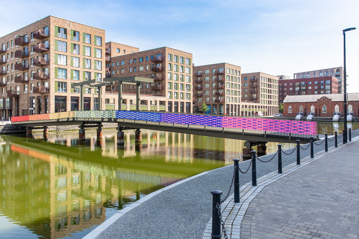 Bridge over Royal Albert Wharf decorated from end to end in rainbow ribbon