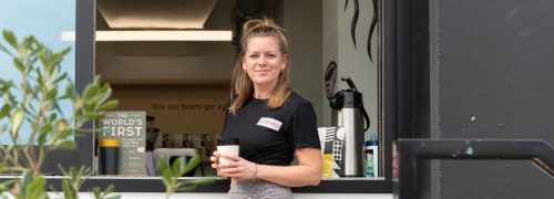 Woman holding coffee outside coffee stall