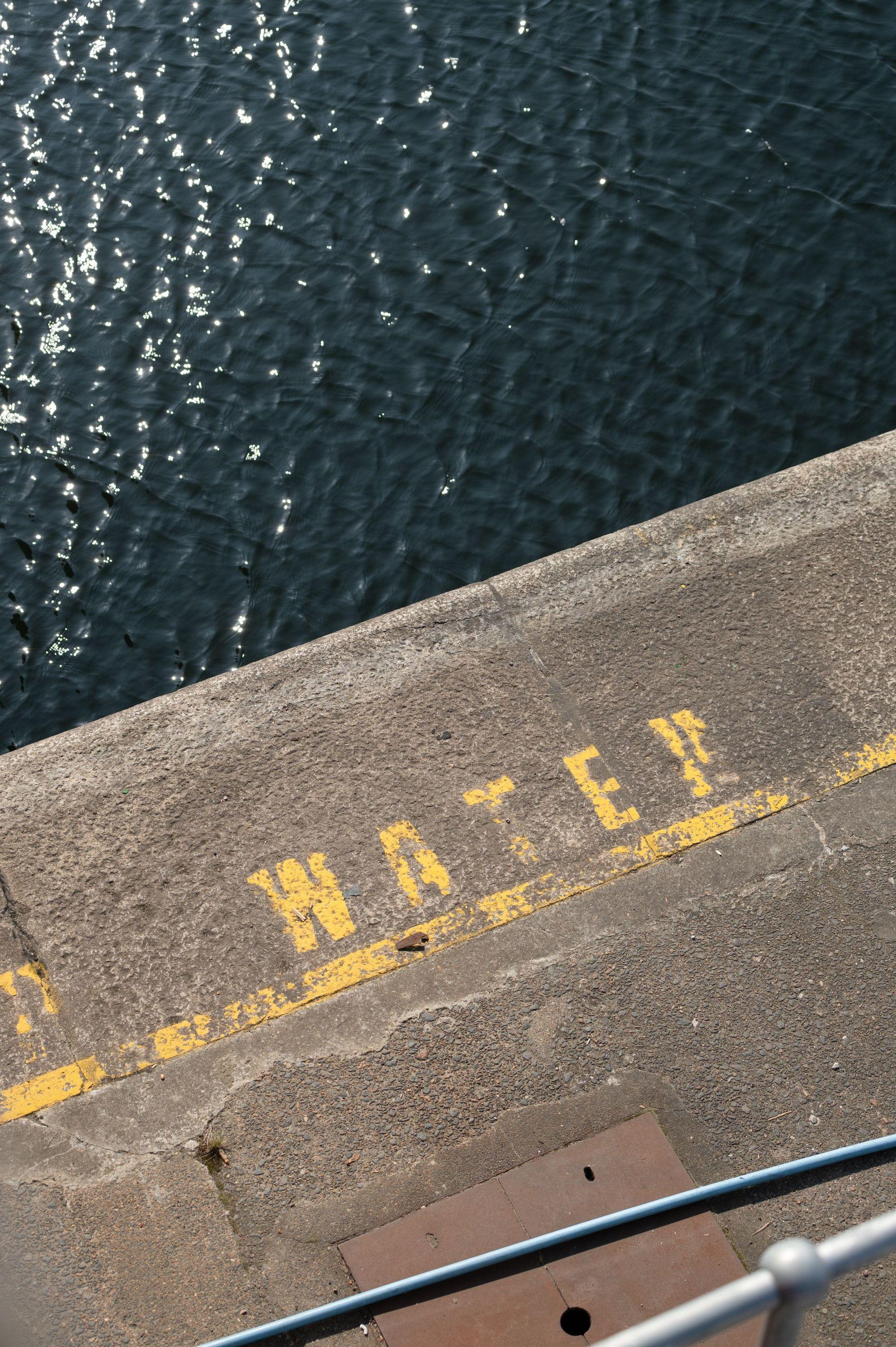 """The dock water seen from above, with the word """"water"""" painted on the edge"""
