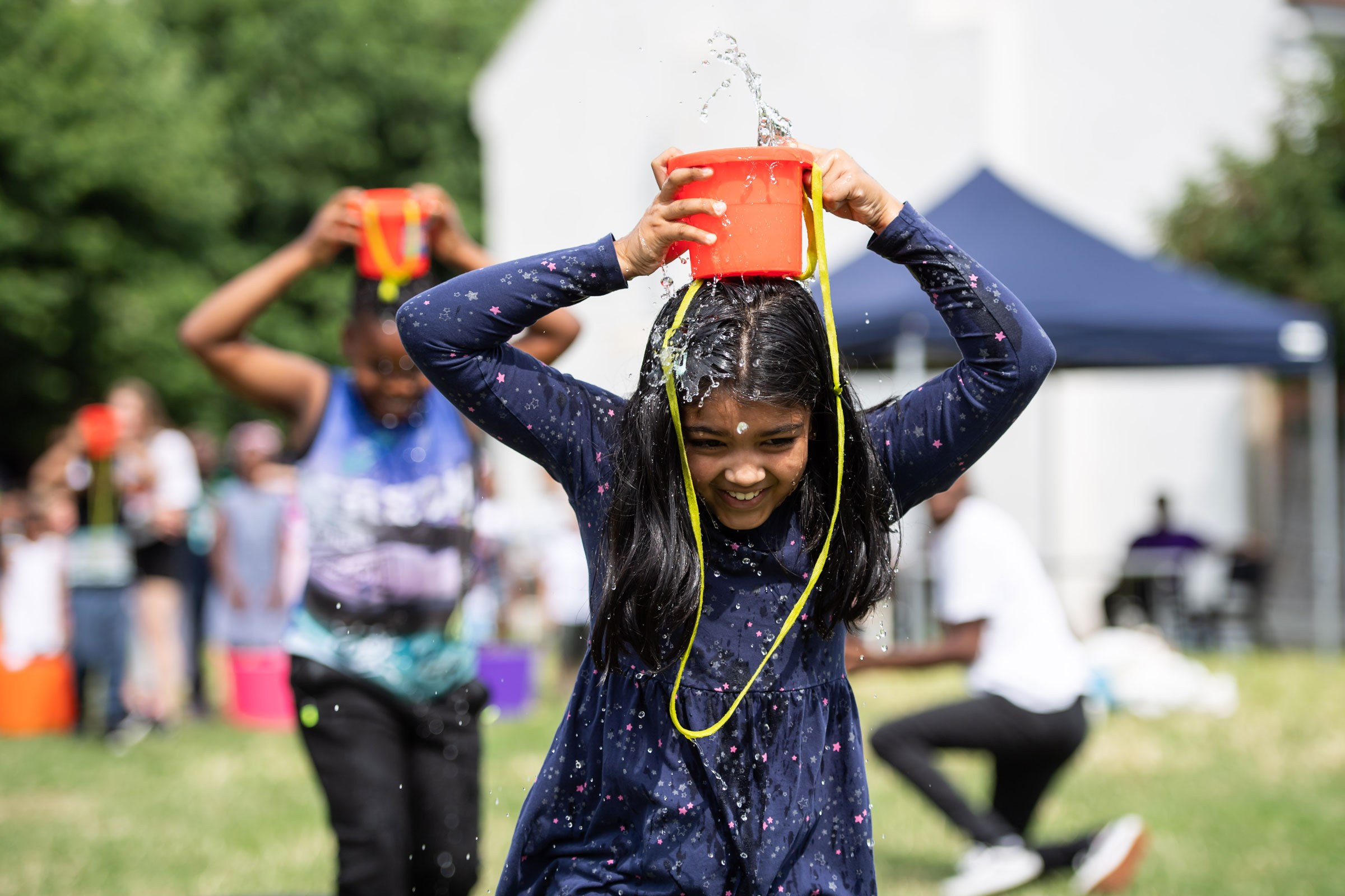 A girl with a bucket of water on her head, laughing