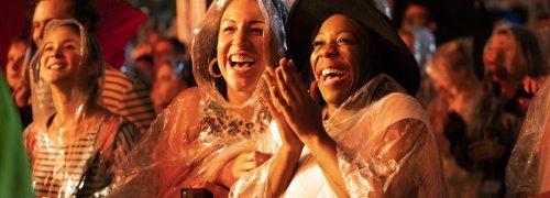 Women in rain coats enjoying an outdoor nighttime show