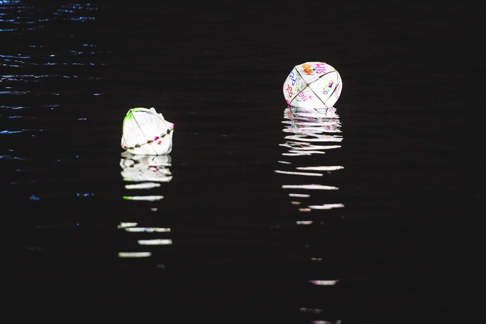 Lanterns floating on water after dark