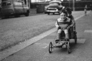 Black and white photo of two young boys go-karting on the street