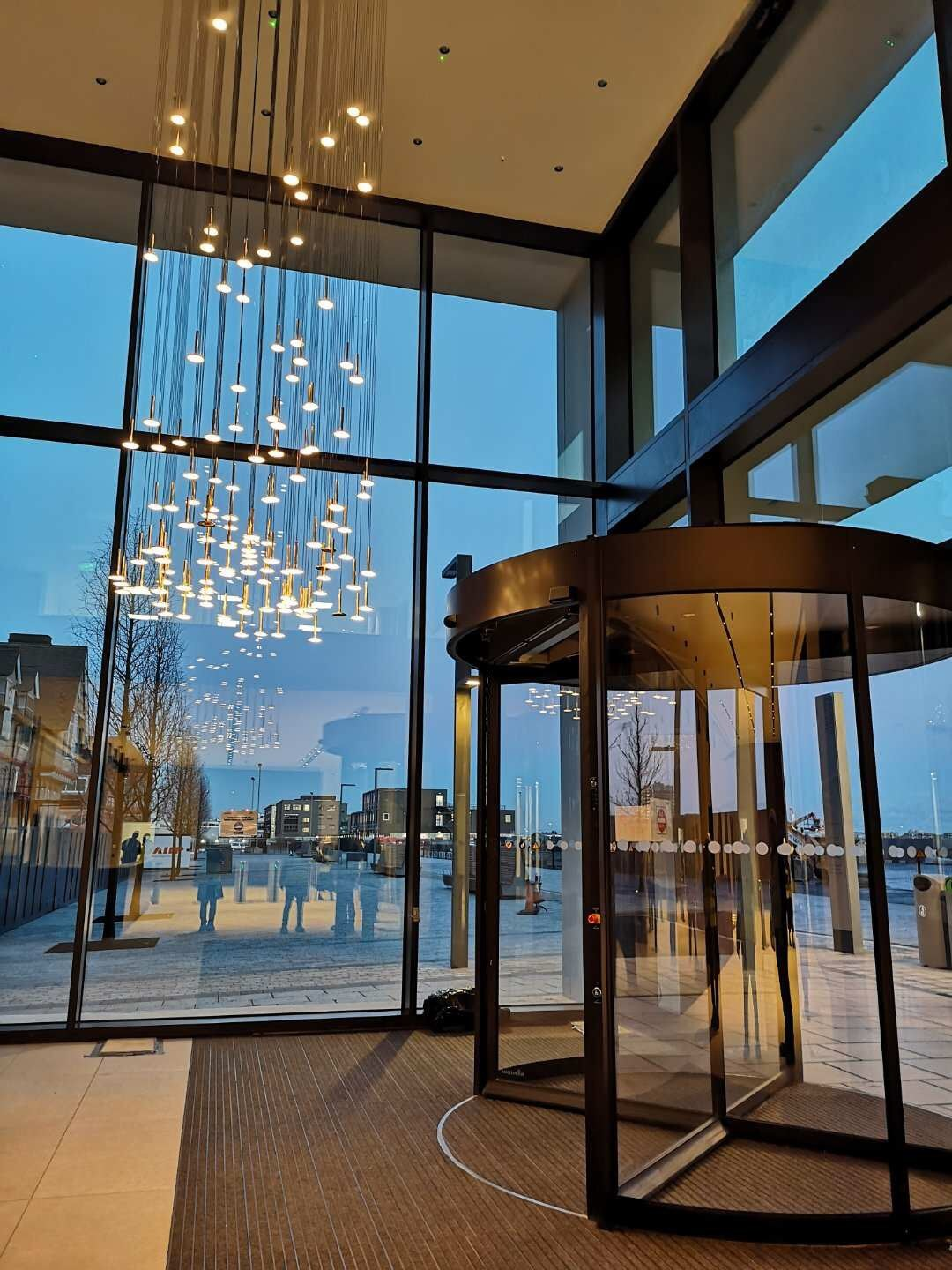 A building entrance with revolving doors on the banks of the Royal Albert Dock
