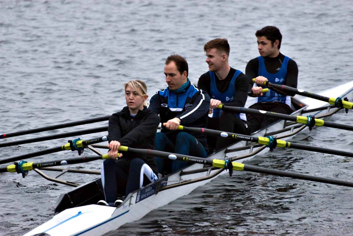 A team of four rowers in a canoe