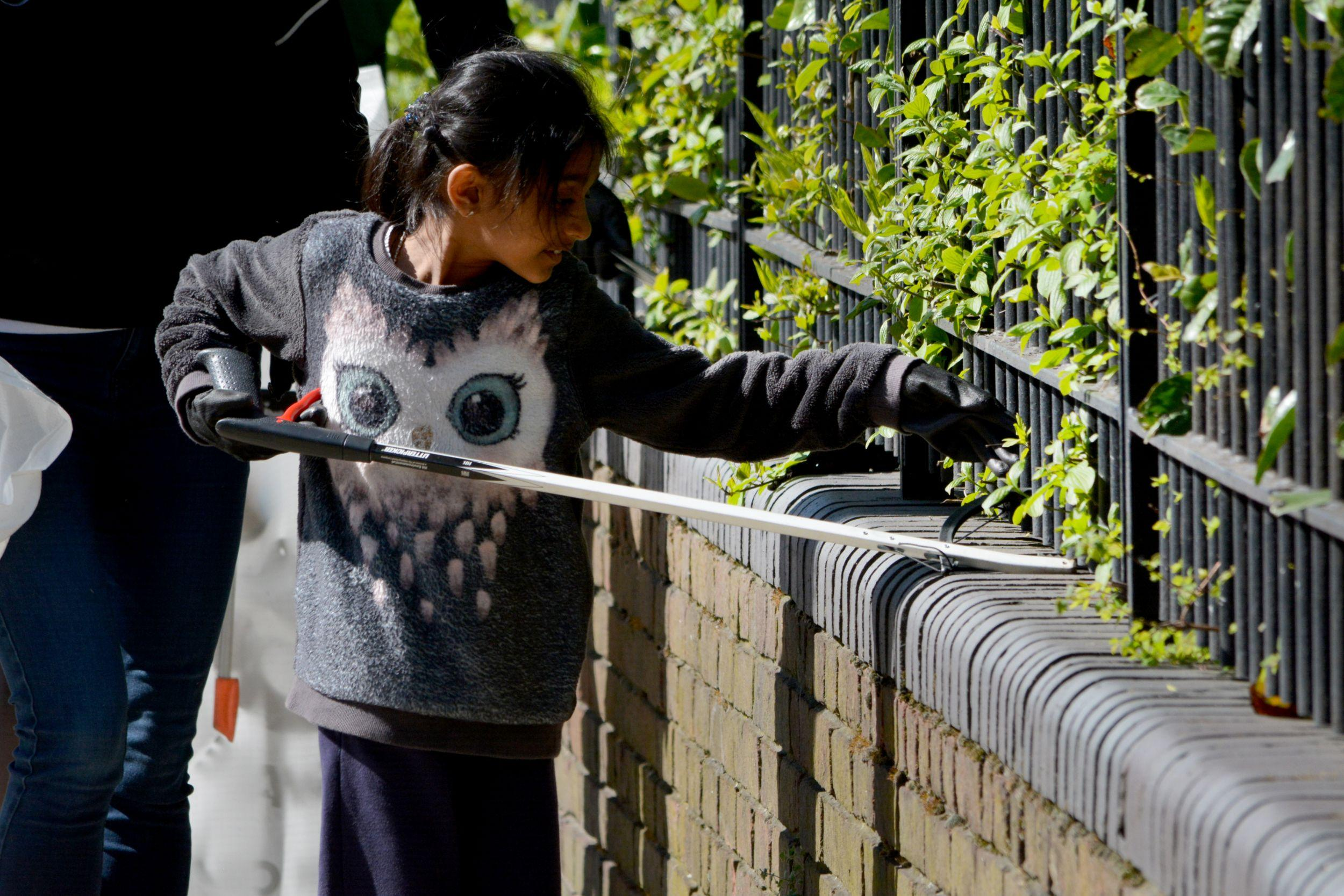 A girl searching for litter between railings