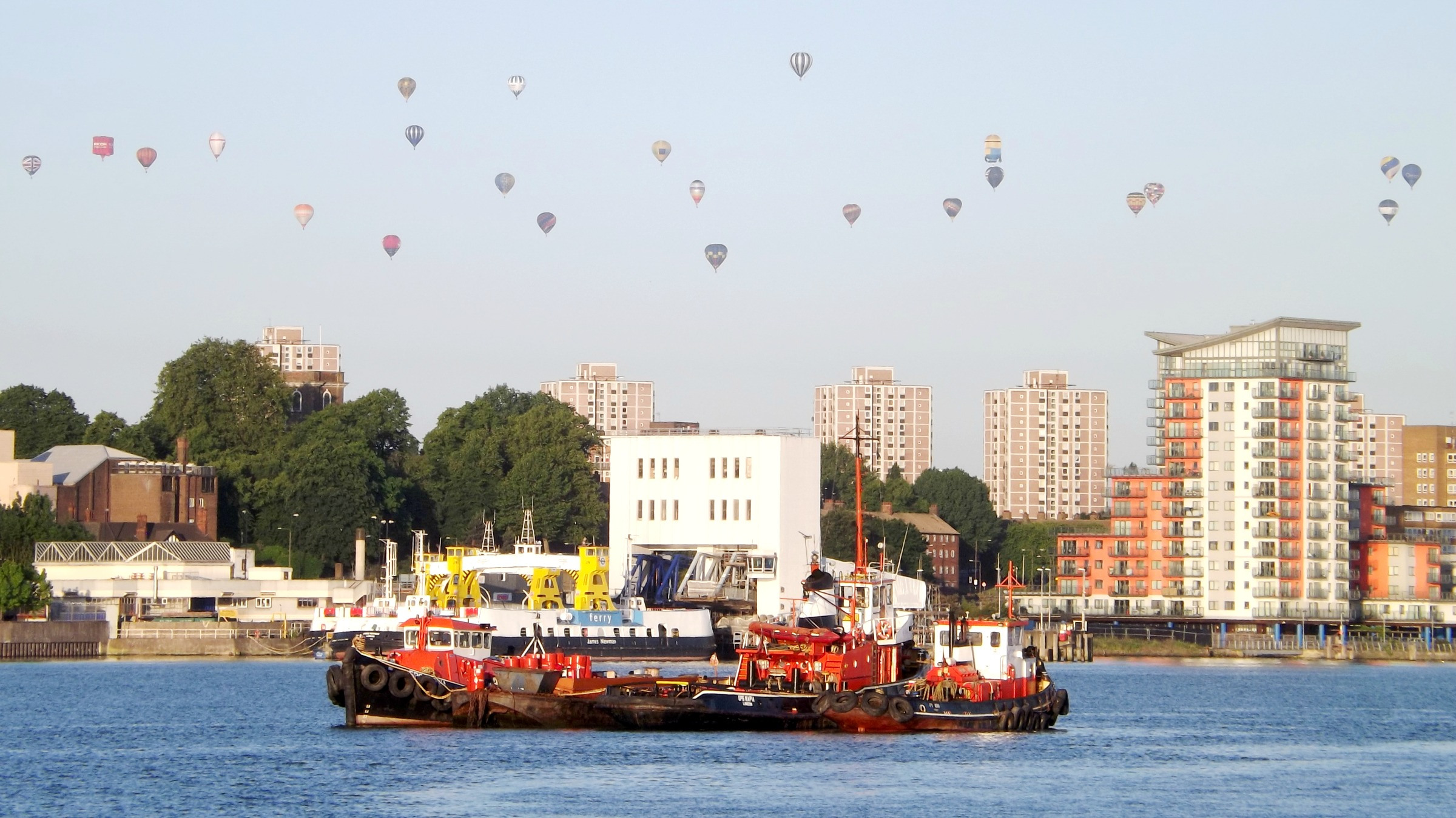 A large group of hot air balloons flying over the Royal Docks