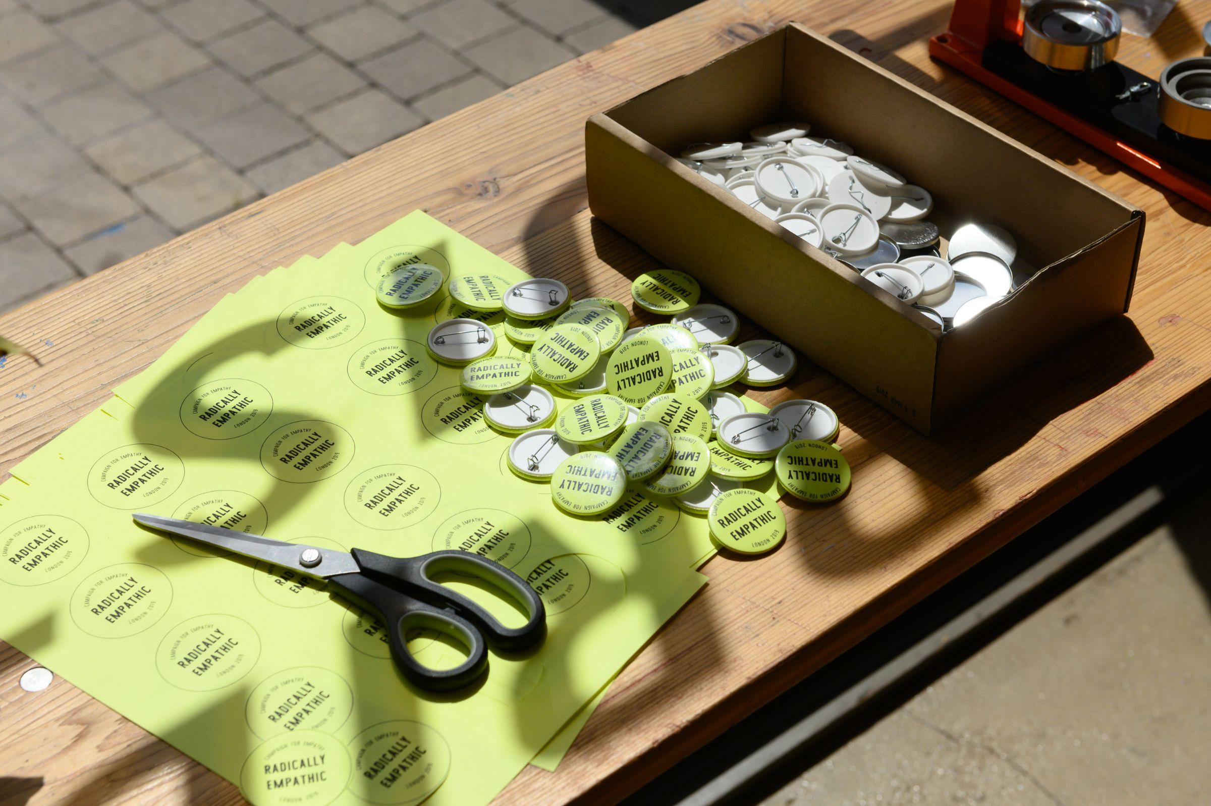 A table with badges and scissors on top of green paper