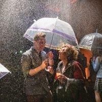 Man and woman under an umbrella in the flavour rainbow, both laughing