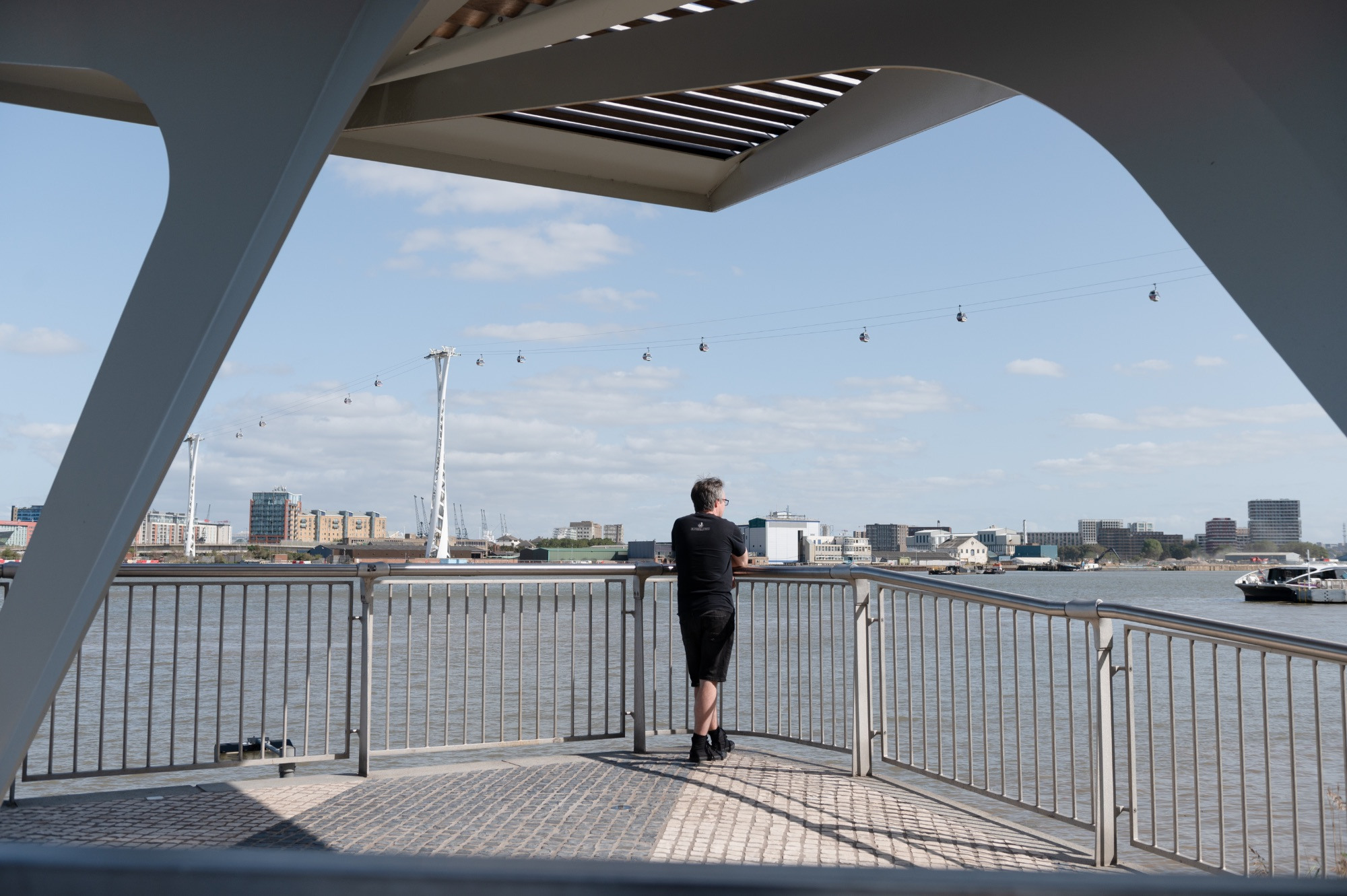 Man looking out at the river from a covered platform, with the cable car in view