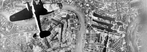 Old photo of a plane seen from above flying over the Thames